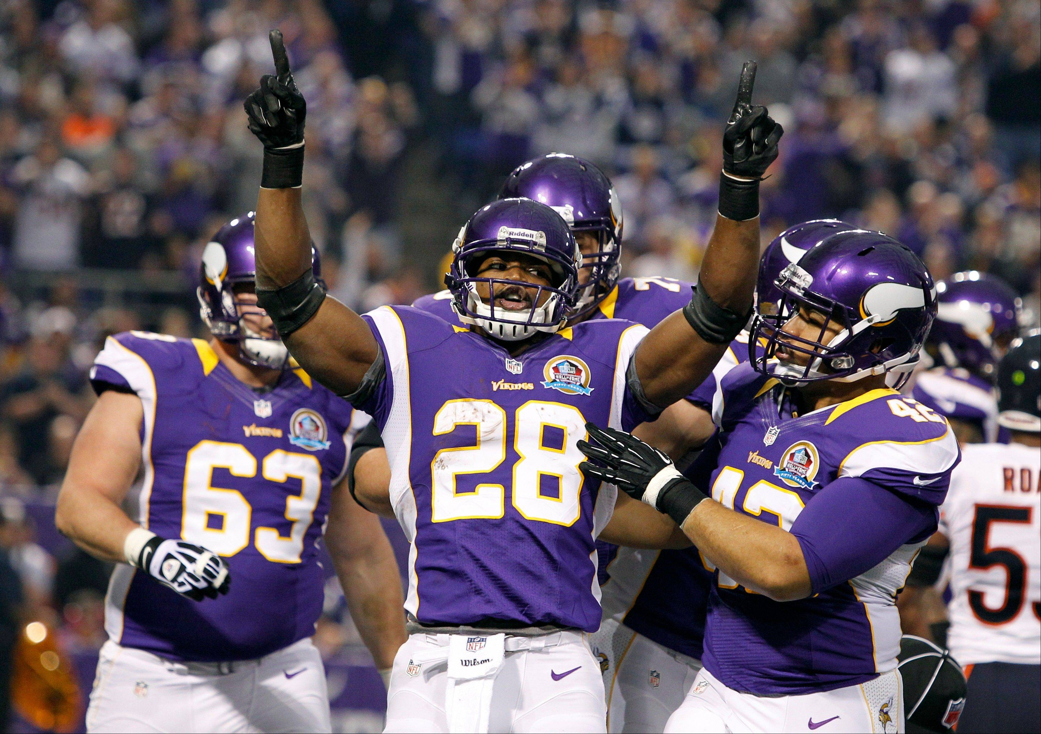Minnesota Vikings running back Adrian Peterson celebrates with teammate Jerome Felton, right, after scoring on a 1-yard touchdown run during the first half.