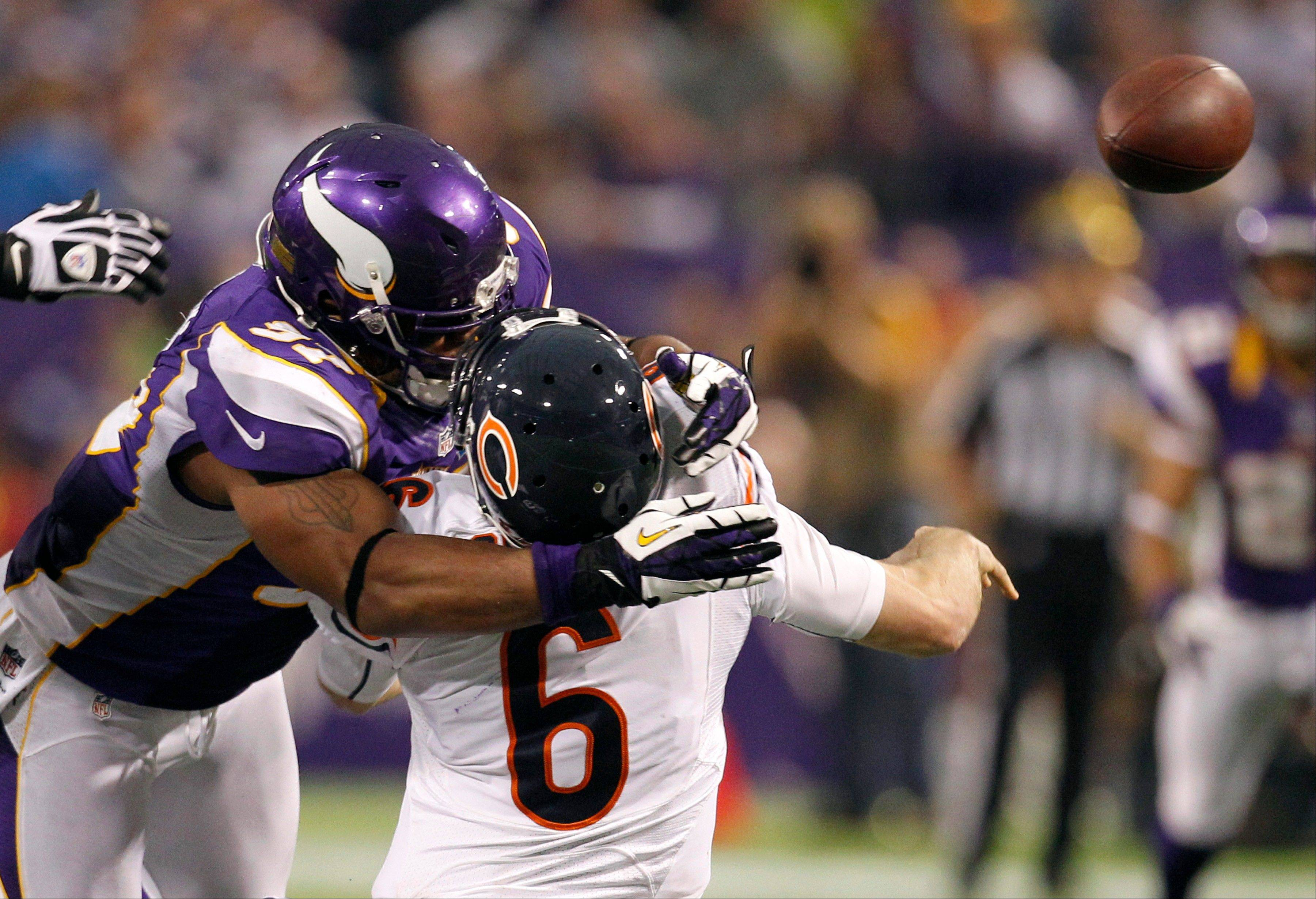 Chicago Bears quarterback Jay Cutler gets hit by Minnesota Vikings defensive end Everson Griffen, left, after passing the ball during the second half. Griffen was called for a personal foul on the play.