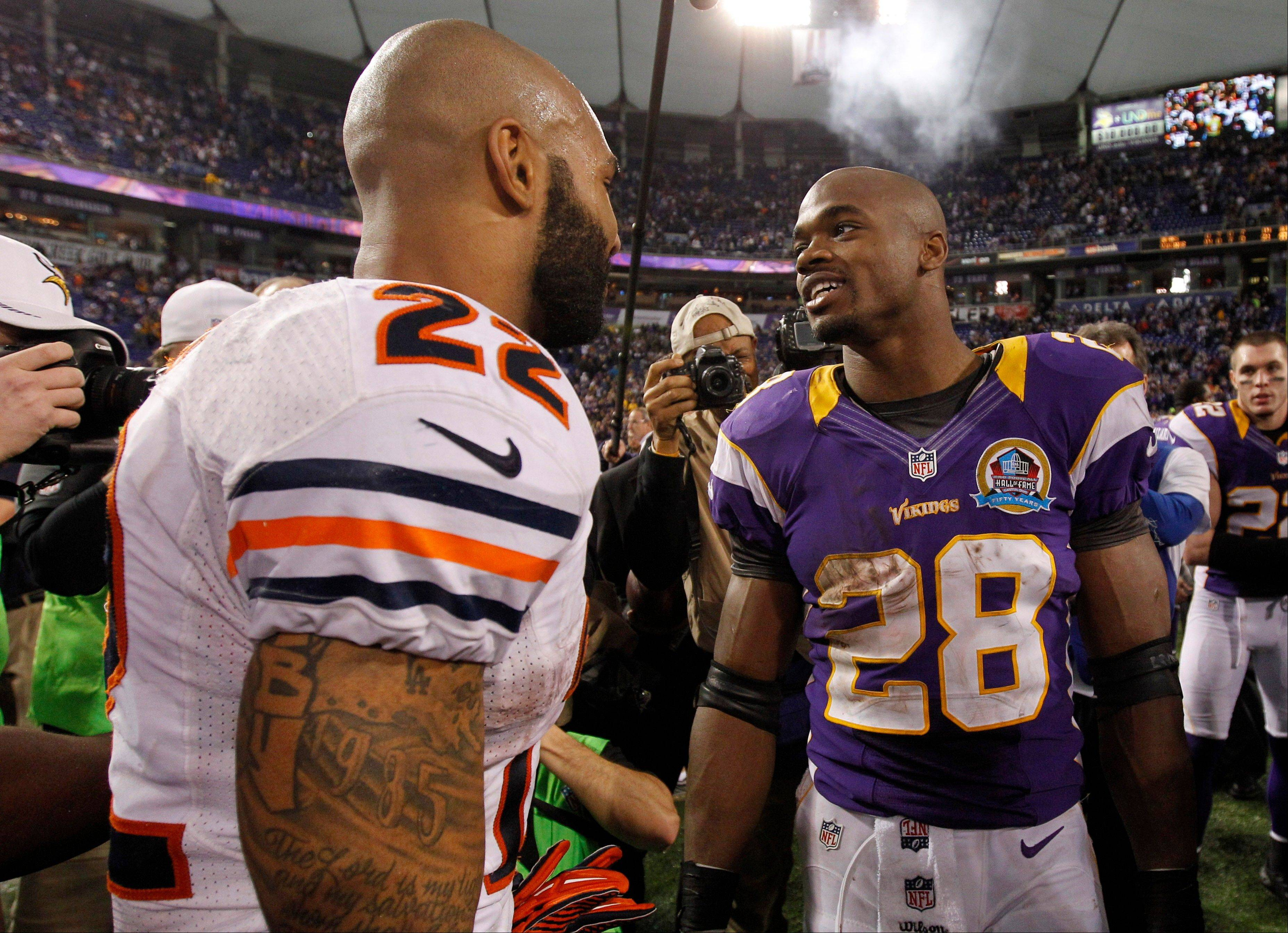 Minnesota Vikings running back Adrian Peterson, right, talks with Chicago Bears running back Matt Forte, left, after an NFL football game. The Vikings won 21-14.