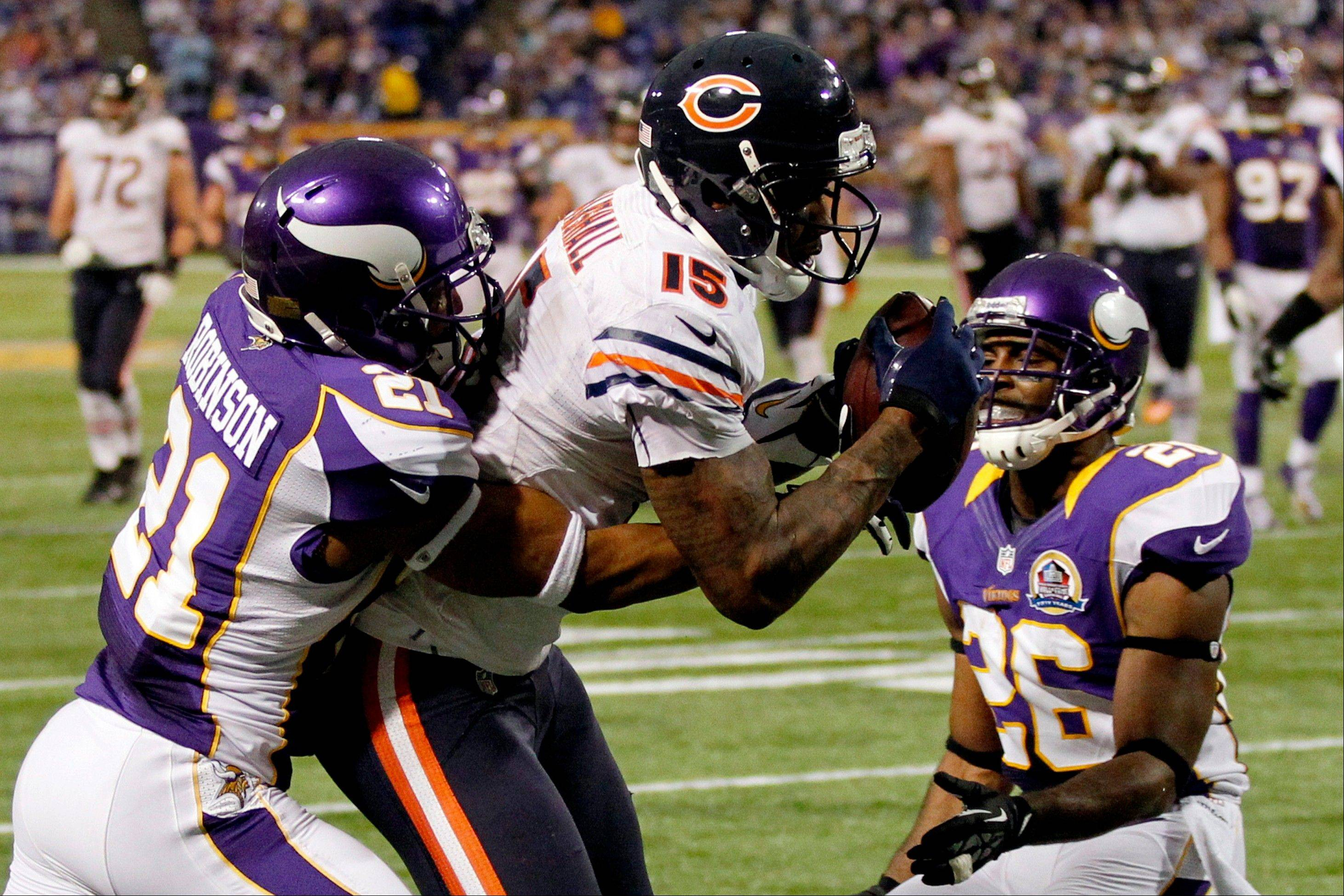 Chicago Bears wide receiver Brandon Marshall, center, catches a 16-yard touchdown pass between Minnesota Vikings cornerback Josh Robinson, left, and cornerback Antoine Winfield, right, during the second half. The Vikings won 21-14.