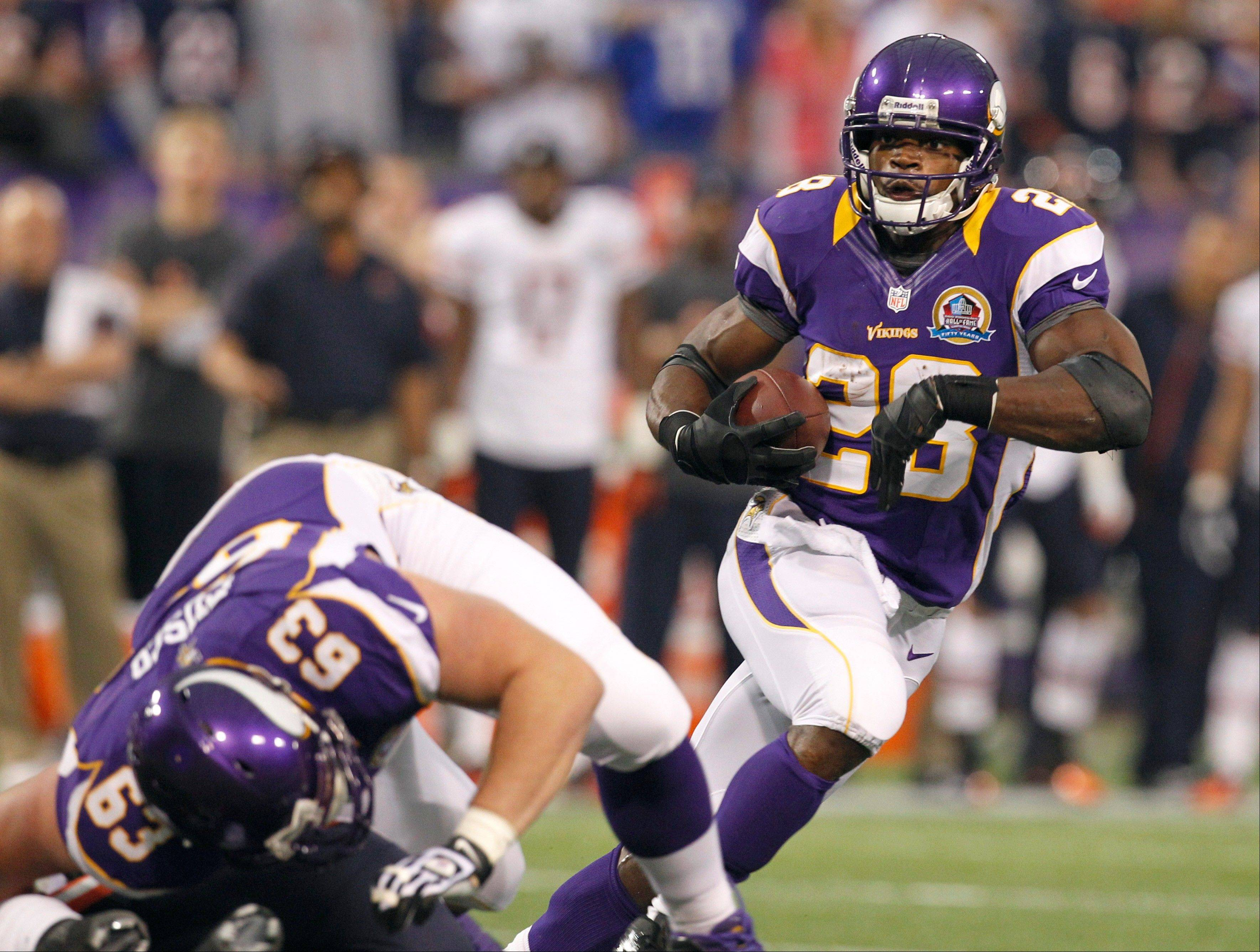 Minnesota Vikings running back Adrian Peterson, right, carries the ball during the first half.