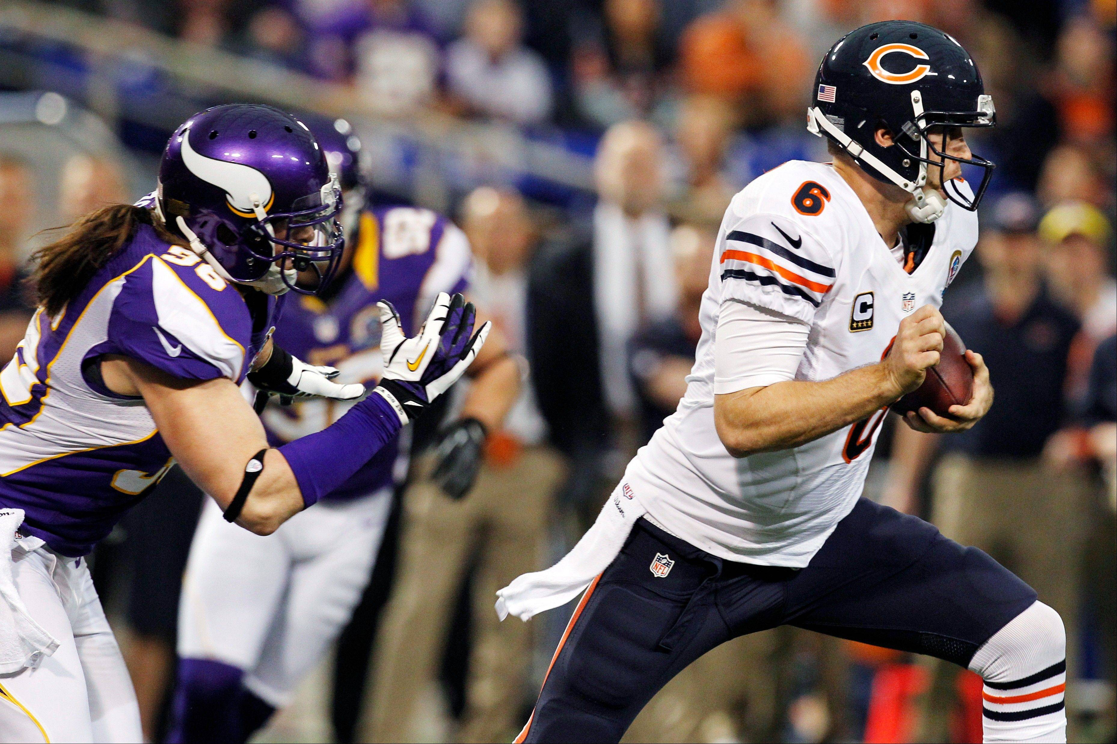 Chicago Bears quarterback Jay Cutler, right, runs from Minnesota Vikings defensive end Brian Robison during the first half.