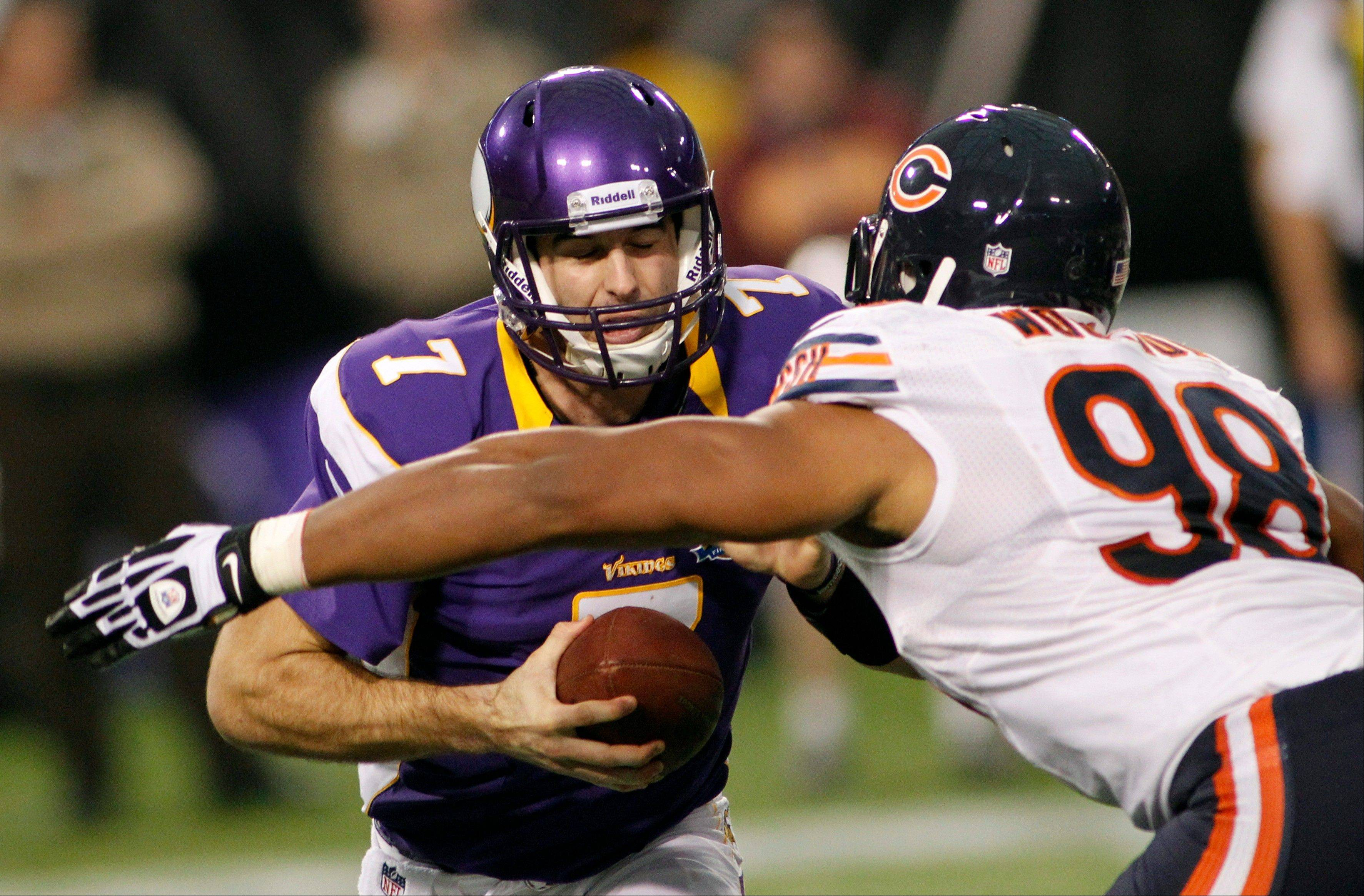 Minnesota Vikings quarterback Christian Ponder, left, is sacked by Chicago Bears defensive end Corey Wootton during the first half.