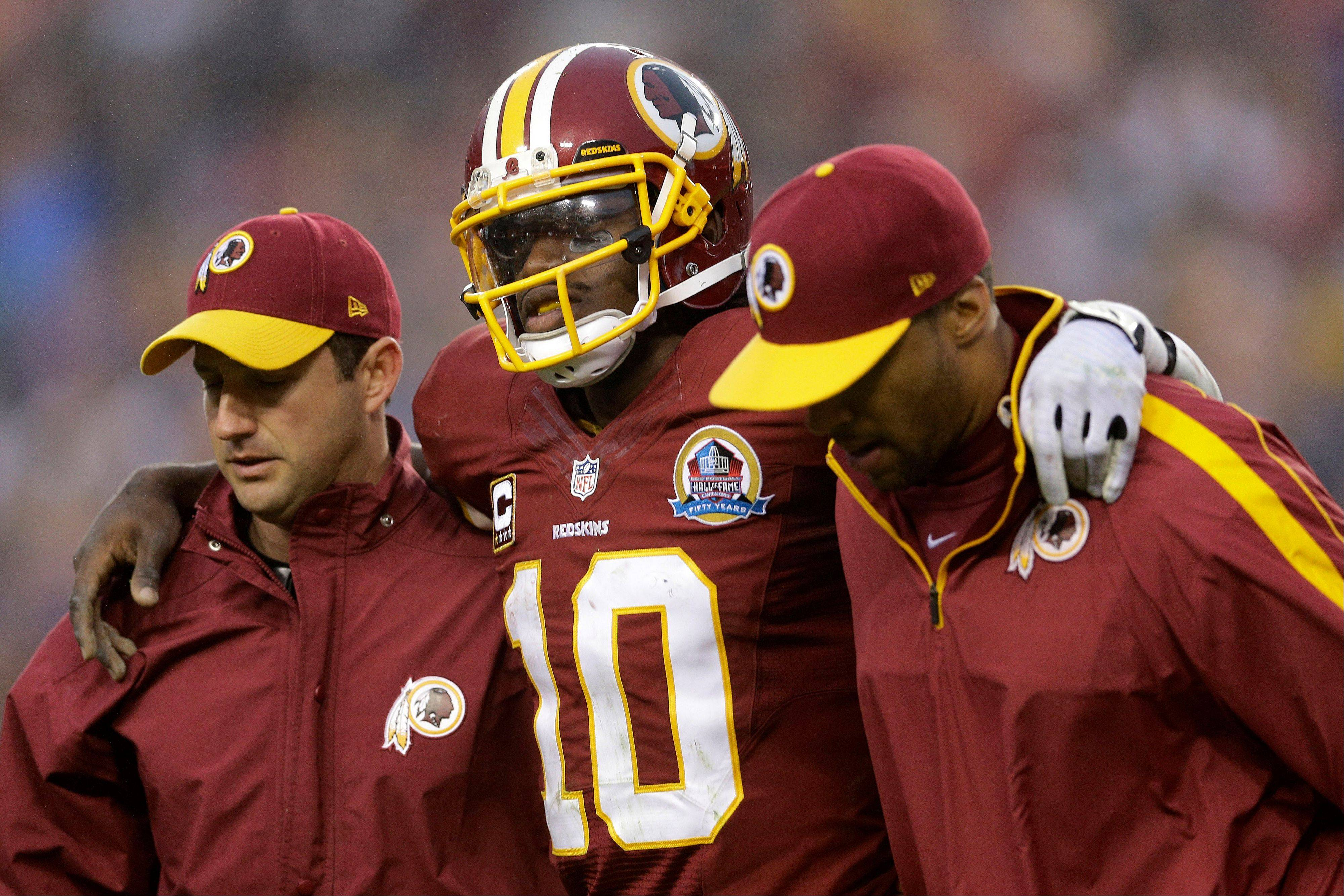 Washington Redskins quarterback Robert Griffin III is helped off the filed after an injury during the second half of an NFL football game against the Baltimore Ravens in Landover, Md., Sunday, Dec. 9, 2012.