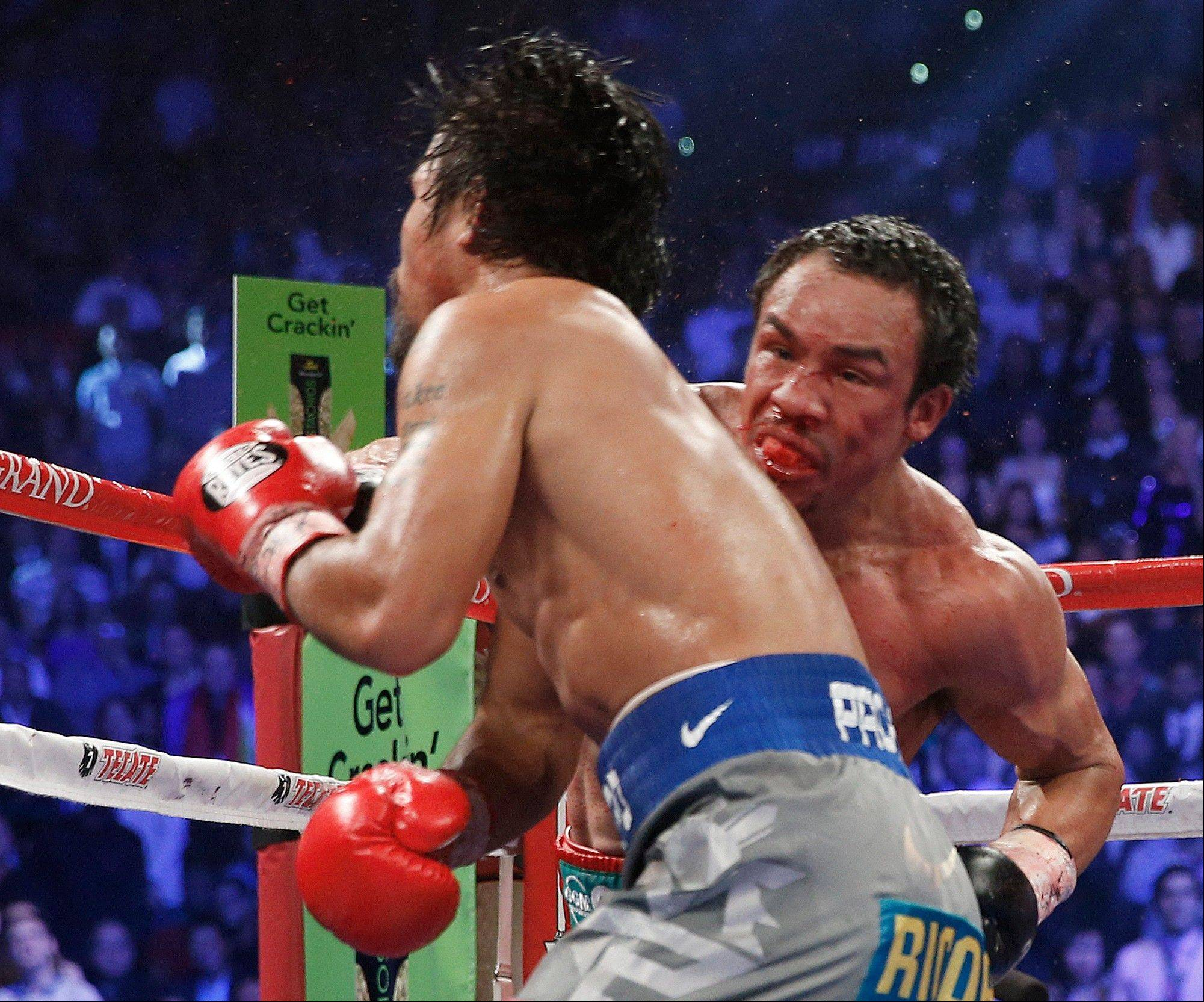 Juan Manuel Marquez, right, knocks out Manny Pacquiao in the sixth round of their WBO world welterweight fight Saturday.