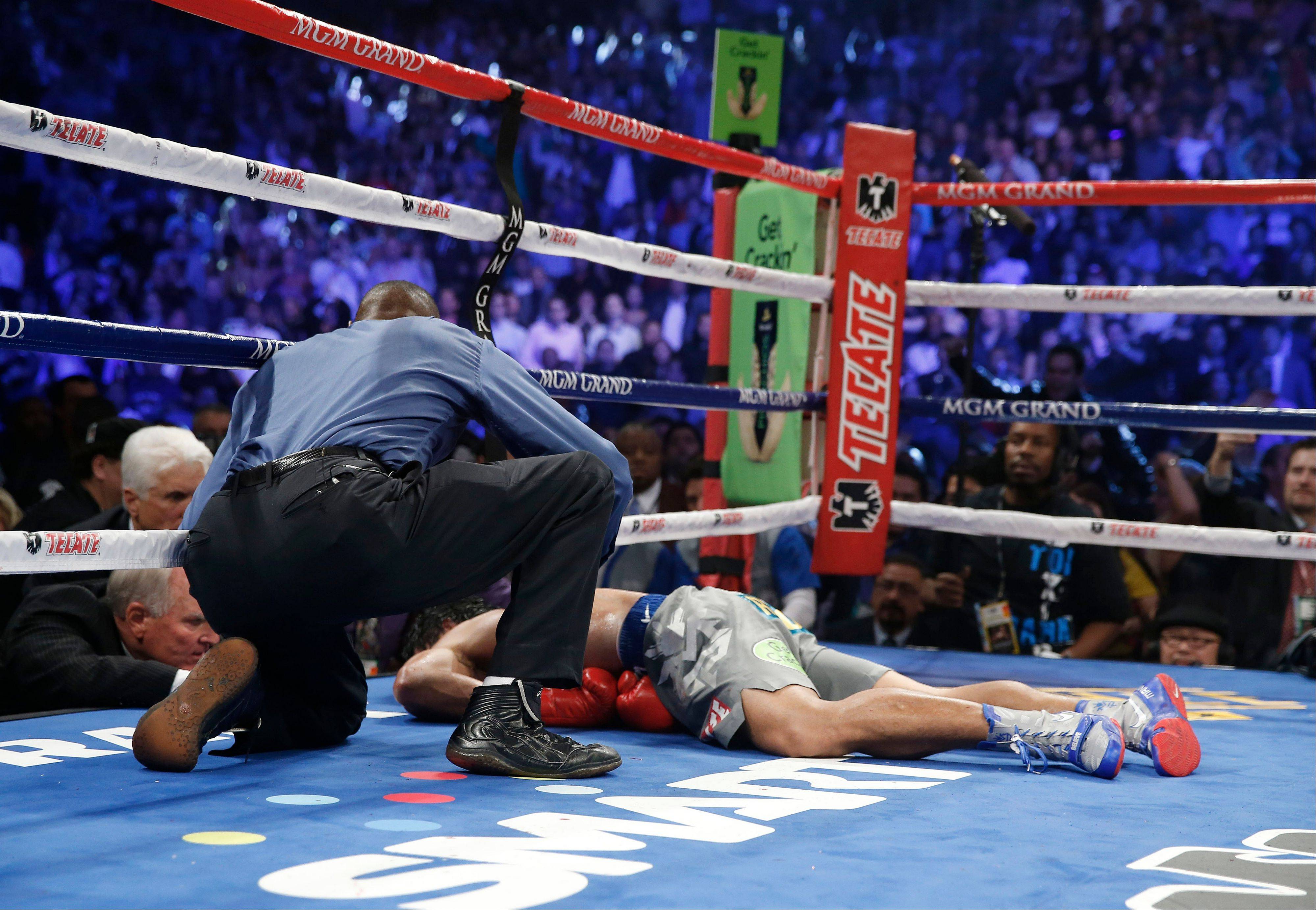 Manny Pacquiao, from the Philippines, lies on the canvas as referee Kenny Bayless kneels nearby after being knocked out by Juan Manuel Marquez, from Mexico, in the sixth round.