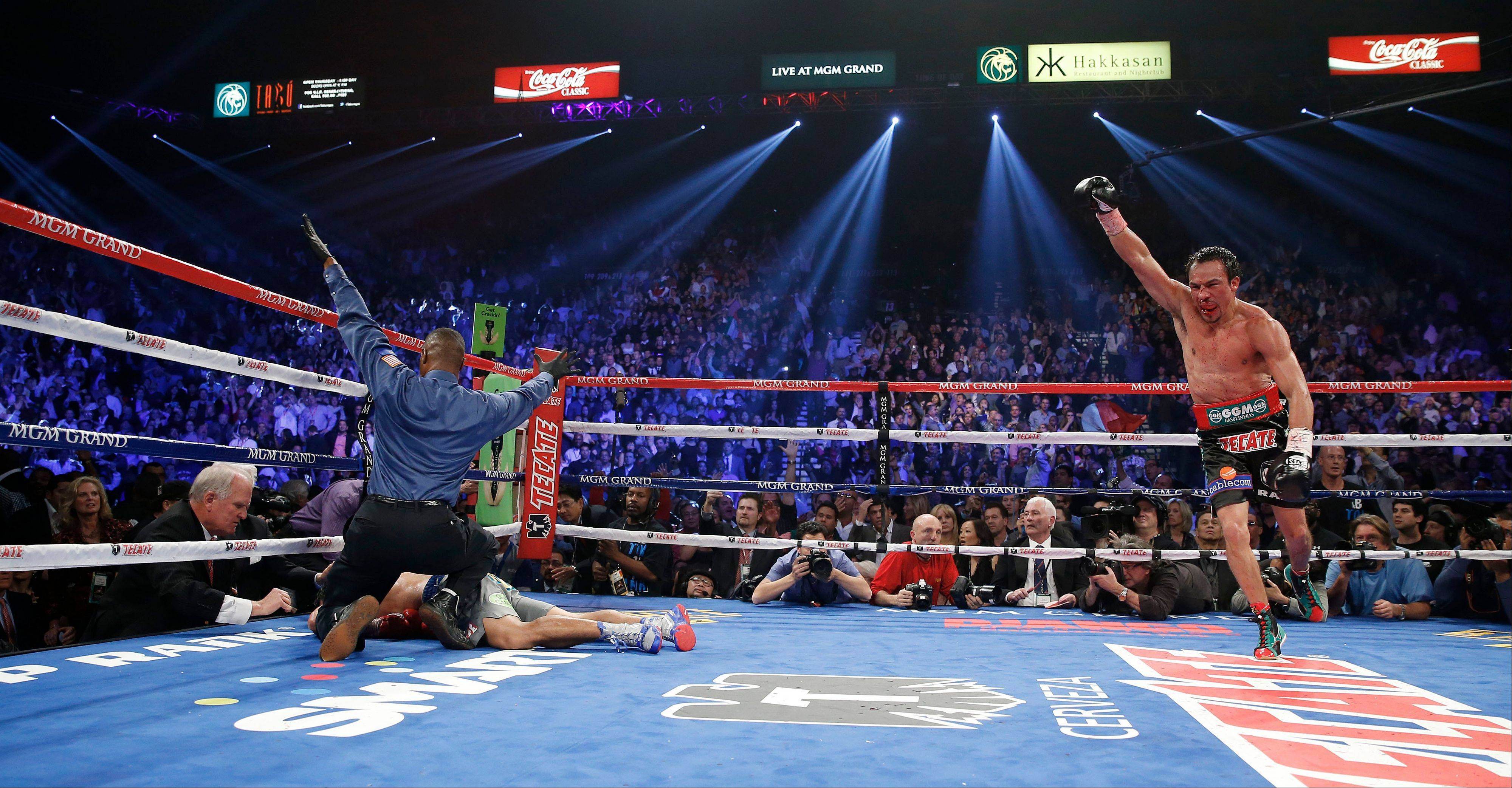 Referee Kenny Bayless, left, calls the fight as Juan Manuel Marquez, from Mexico, right, celebrates after he knocked out Manny Pacquiao, from the Philippines.