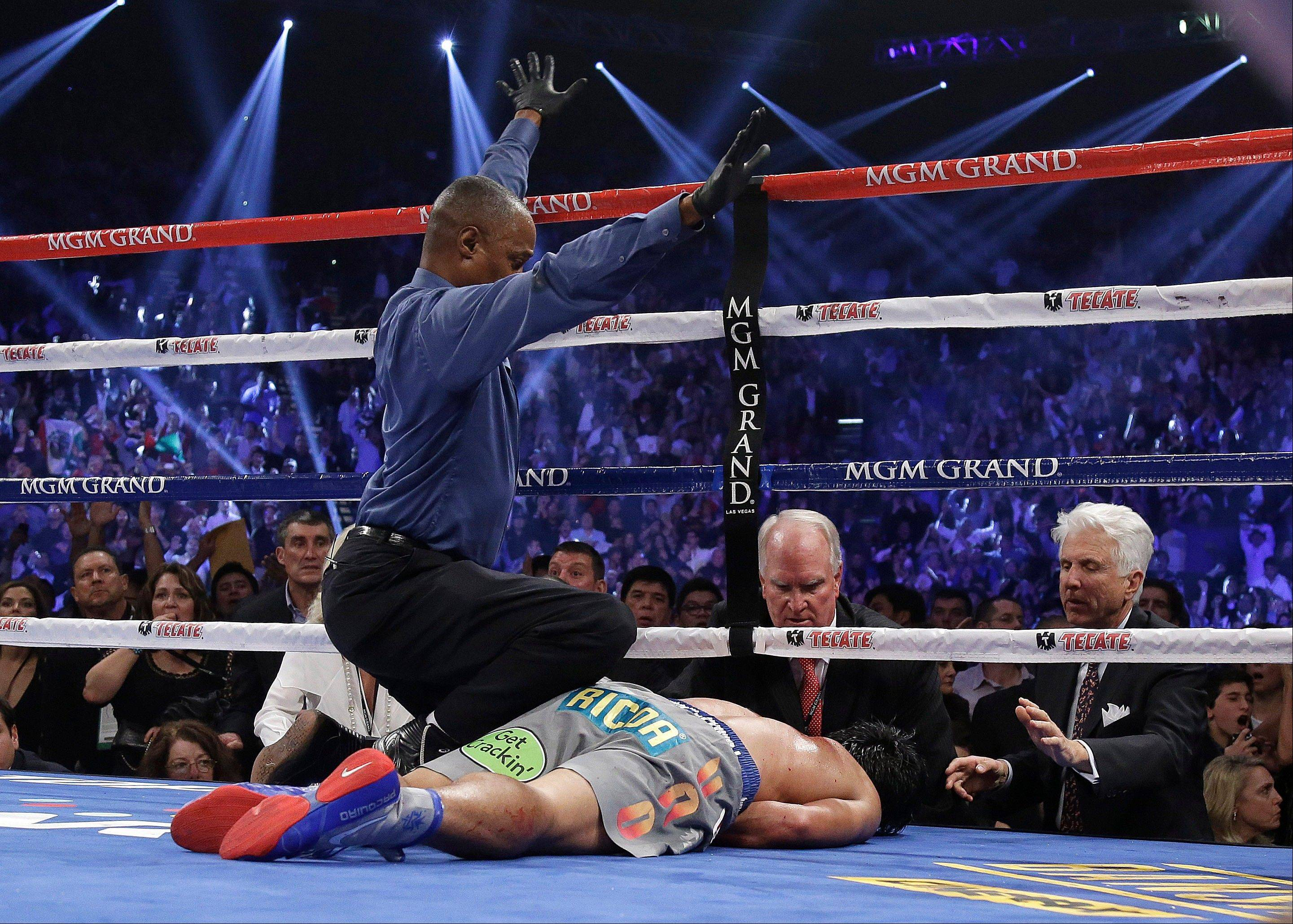 Referee Kenny Bayless calls the fight as he kneels over Manny Pacquiao after he was knocked out by Juan Manuel Marquez.