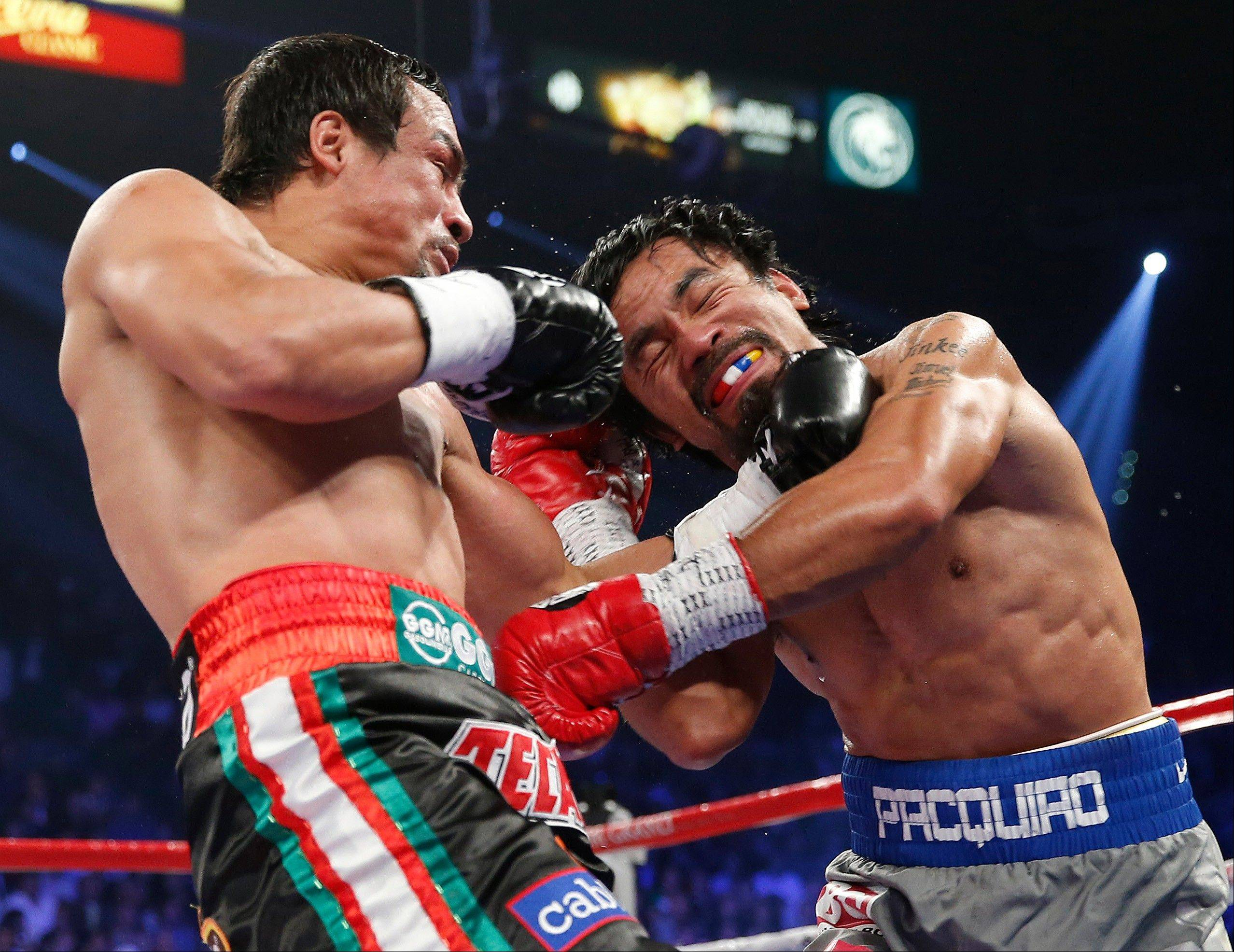Juan Manuel Marquez, left, and Manny Pacquiao trade blows.