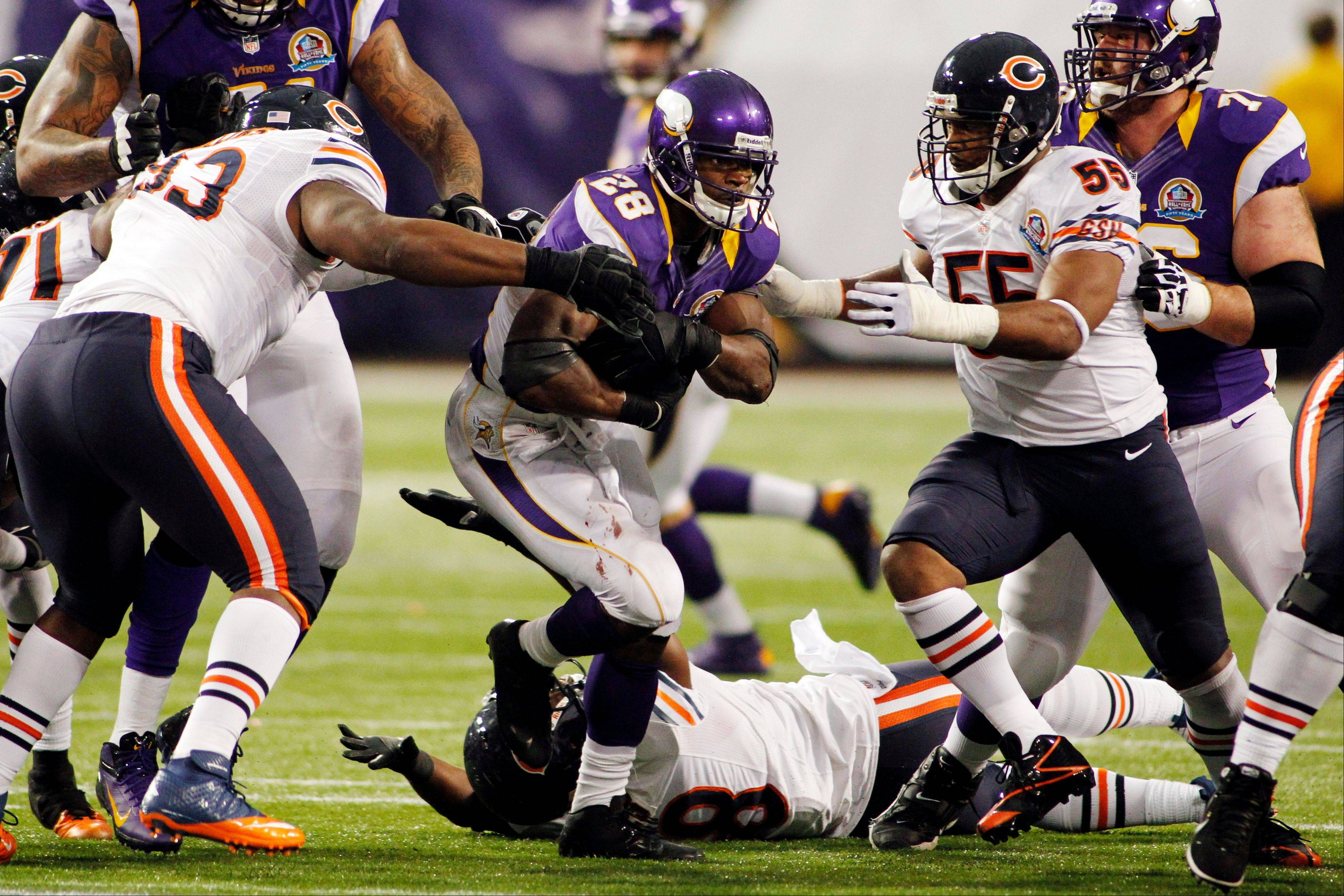 Vikings running back Adrian Peterson (28) rushes between Chicago Bears' Nate Collins, left, and Lance Briggs, right, during the second half of an NFL football game, Sunday, Dec. 9, 2012, in Minneapolis. The Vikings won 21-14.