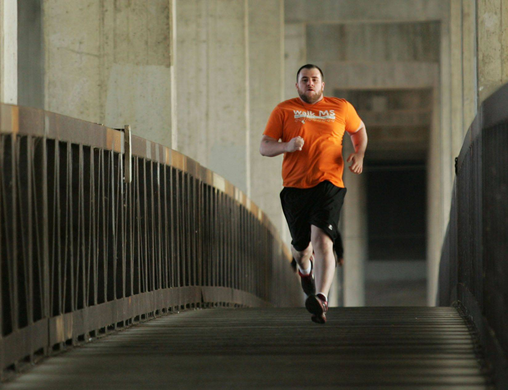 Michael White, 2012 Fittest Loser Challenge winner, runs at one of his favorite spots, the bridge above the Fox River in Elgin near Voyageurs Landing Forest Preserve.
