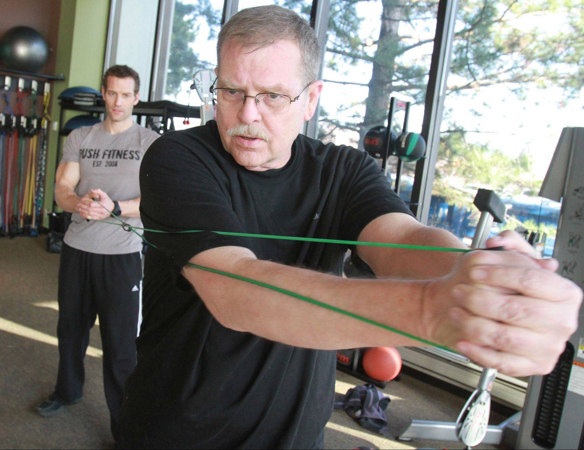 Joshua Steckler, trainer and co-owner of Push Fitness in Schaumburg, works out with Tom Hampson. After completing the competition in May, Hampson continues to train with Steckler.