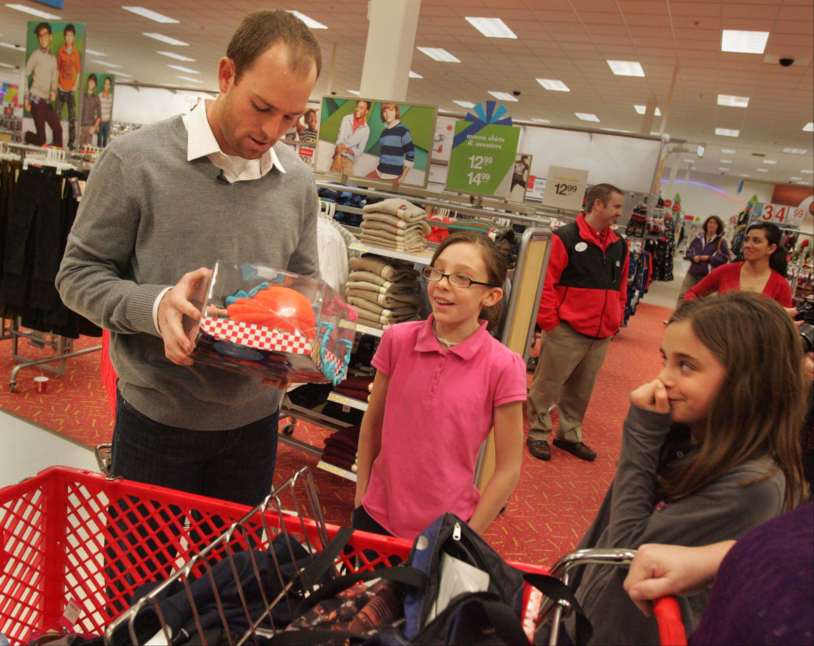Bears kicker Robbie Gould checks out the gifts picked out by Mooseheart students Suriah Randolph, 11, center, and Autumn O'Neal, 9, during the kids' shopping trip at Super Target Monday in St. Charles. Gould, for the second straight year, showed up to help Mooseheart kids shop for Christmas, a project funded by his charity The Goulden Touch.