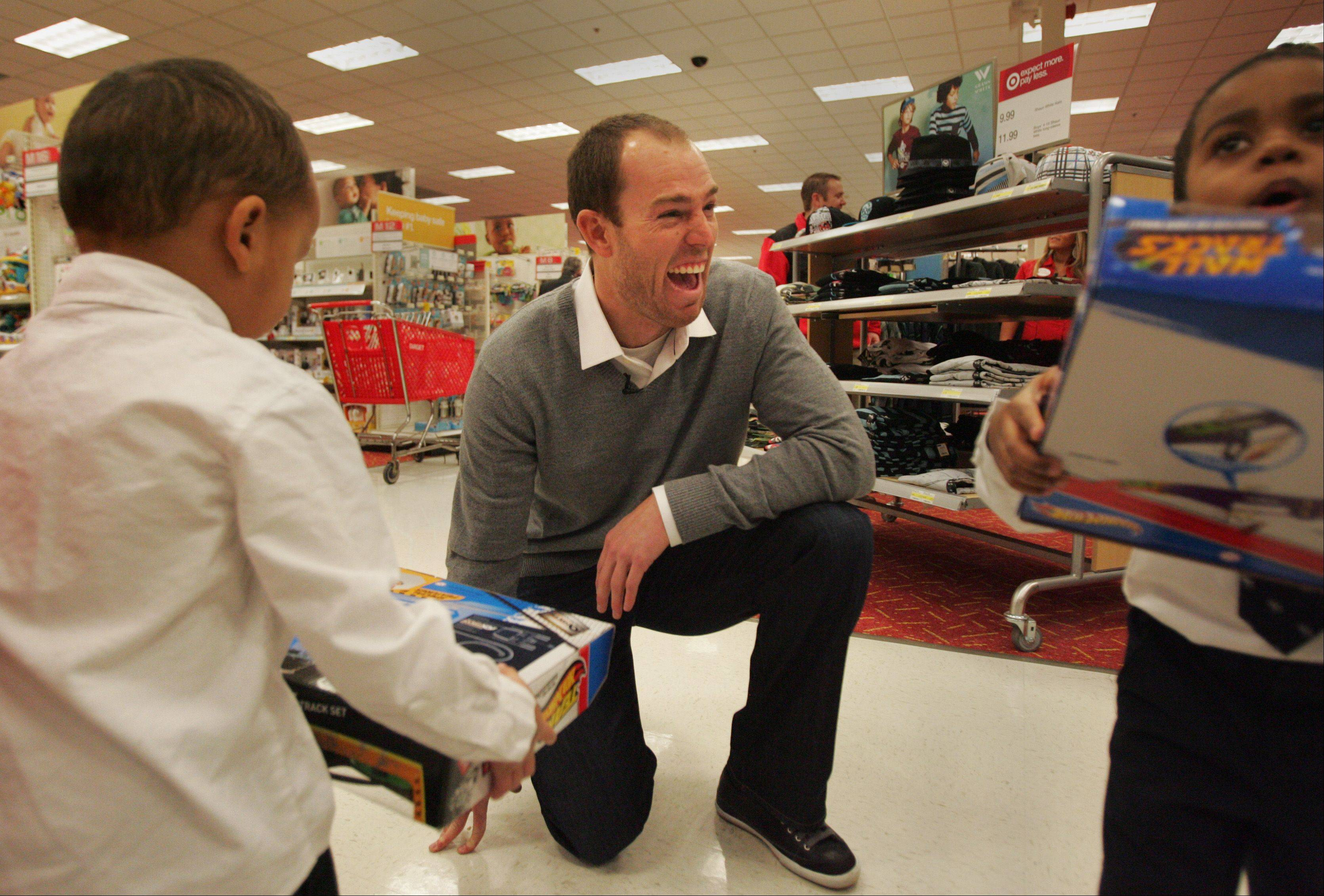 Bears kicker Robbie Gould gets a huge laugh out of talking with Mooseheart kids Isaak Babadjide, left, and Jaylon Moore as they tell him about the toys they picked out. Both boys are 3 years old. Gould, for the second straight year, showed up to help Mooseheart kids shop for Christmas at the Super Target store in St. Charles Monday afternoon, a project funded by his charity The Goulden Touch.