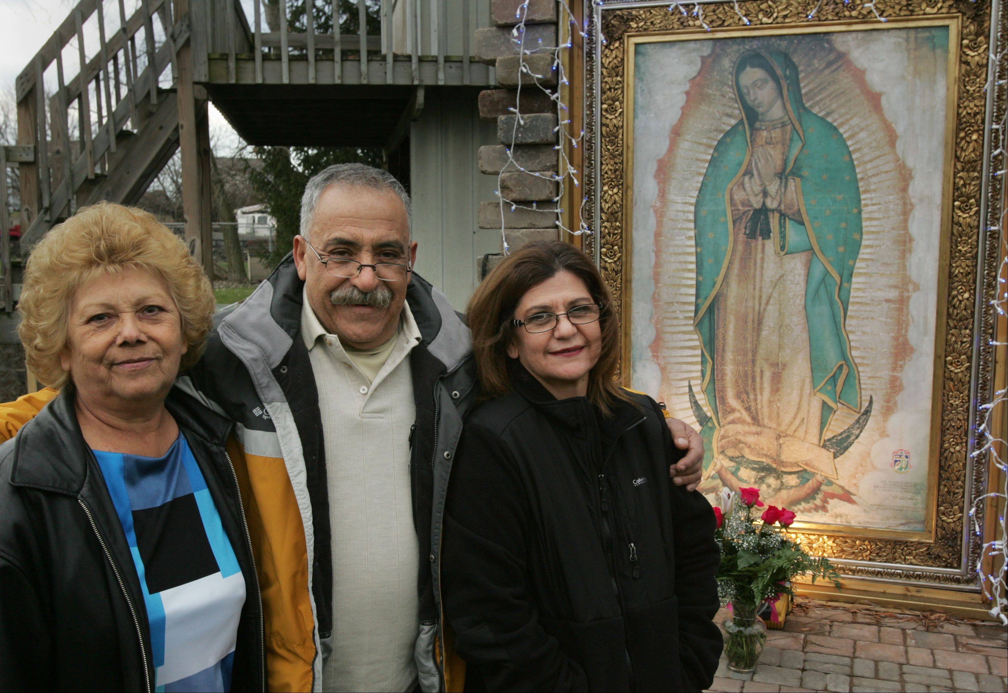 Al Nava and his wife, Fabby, right, have an exact replica of the Virgin of Guadalupe on display in the backyard of their Elgin home. Also pictured is Rosalinda Padilla of Elgin, a close family friend of the Navas.