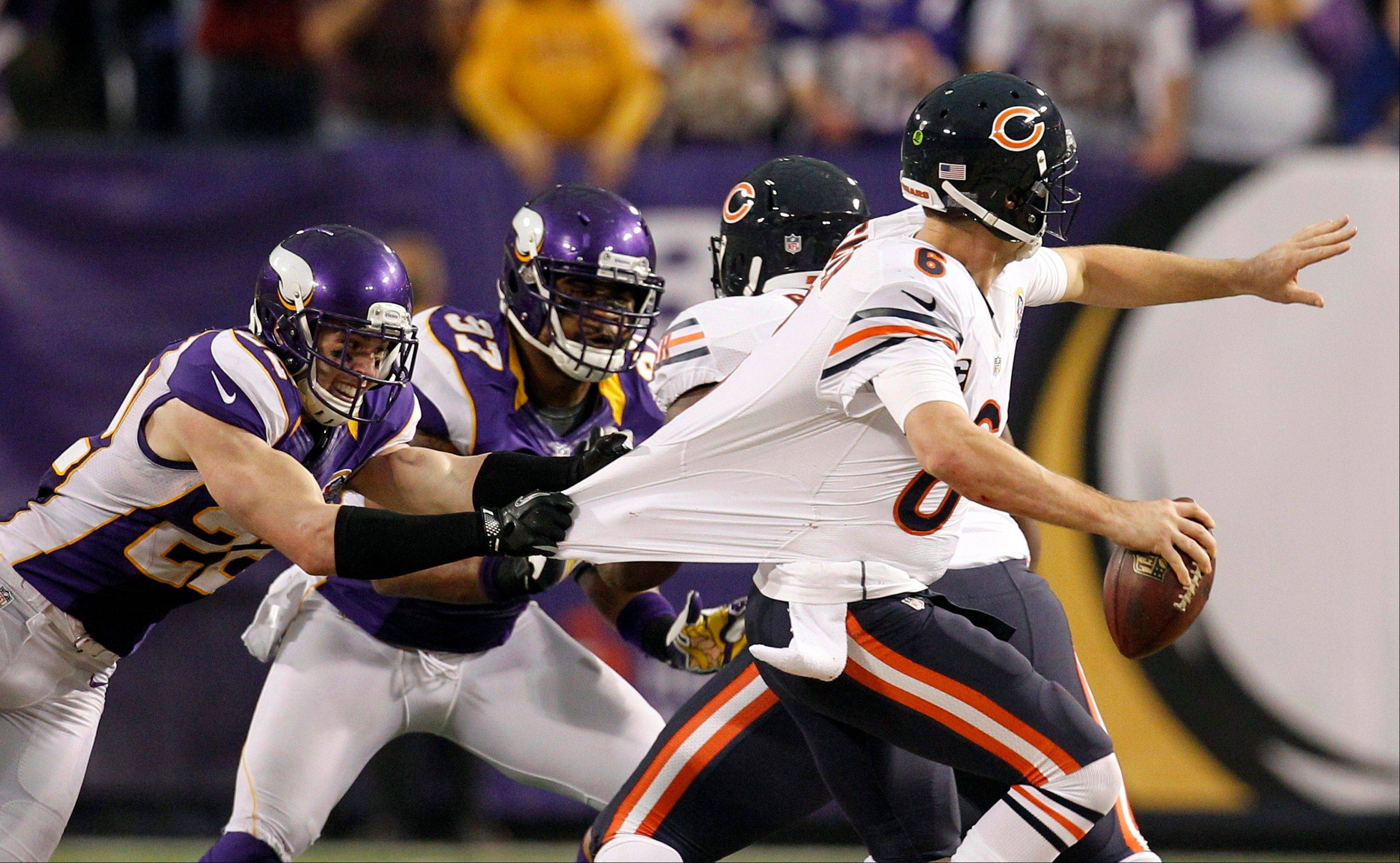 "Chicago Bears quarterback Jay Cutler, right, runs from Minnesota Vikings safety Harrison Smith, left, and defensive end Everson Griffen (97) during the second half of an NFL football game Sunday, Dec. 9, 2012, in Minneapolis. Cutler would leave the game early with what team officials called ""whiplash."""