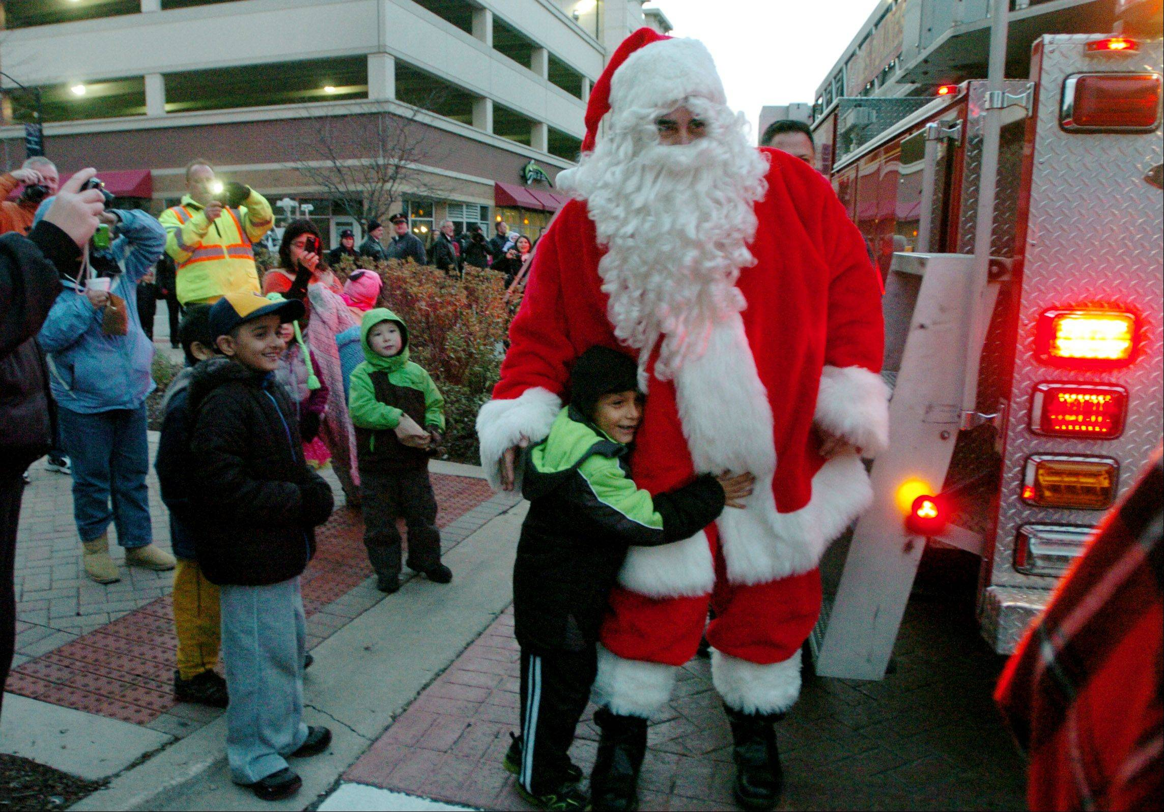 6-year-old Andrew Hernandez of Orchard School is one of the first kids to greet Santa after arriving on a fire truck during the Des Plaines annual Christmas tree lighting event in Metropolitan Square.