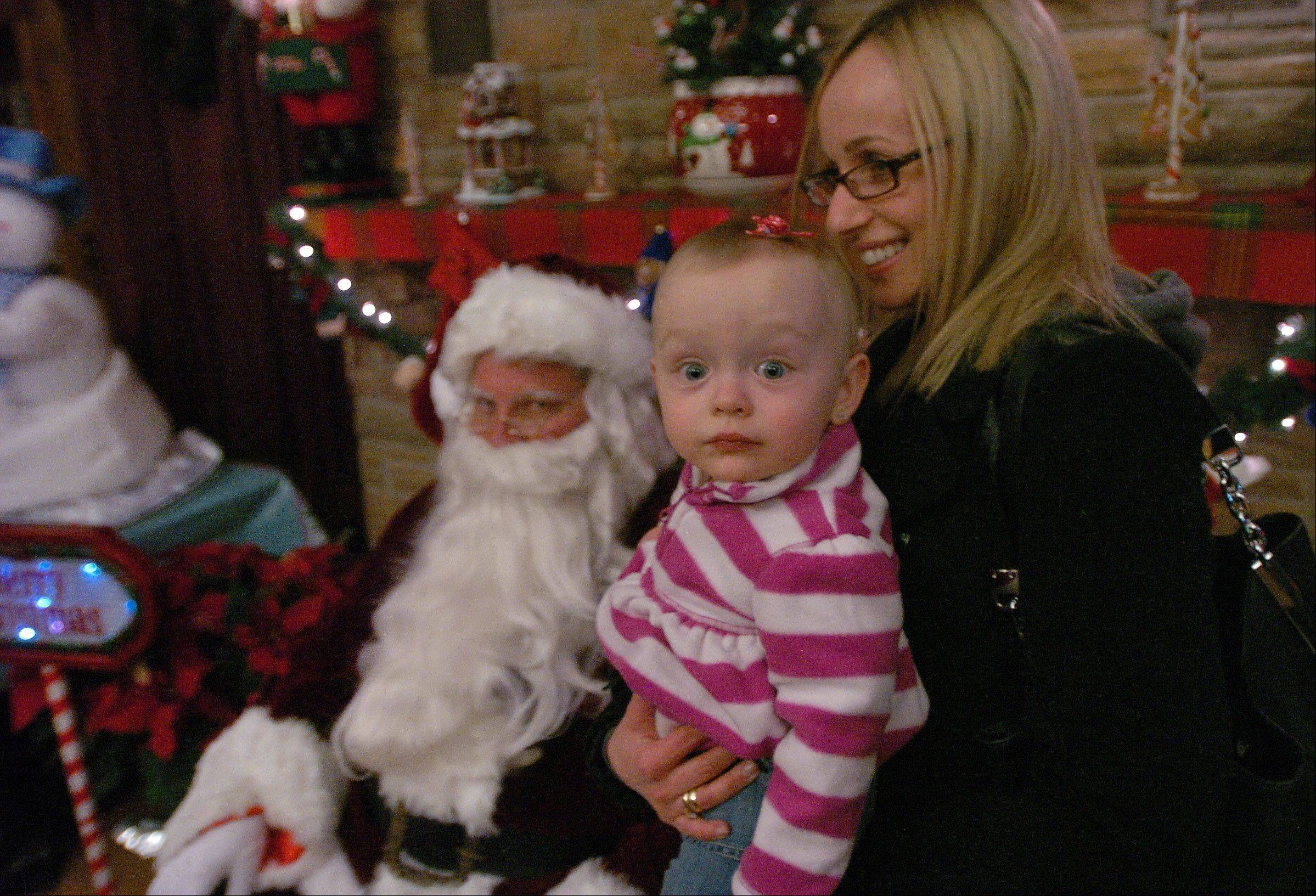 16-month-old Zuzanna Derendar visits Santa in the Log Cabin with her mom Gaba Derendar, prior to the tree lighting in Bartlett Park.
