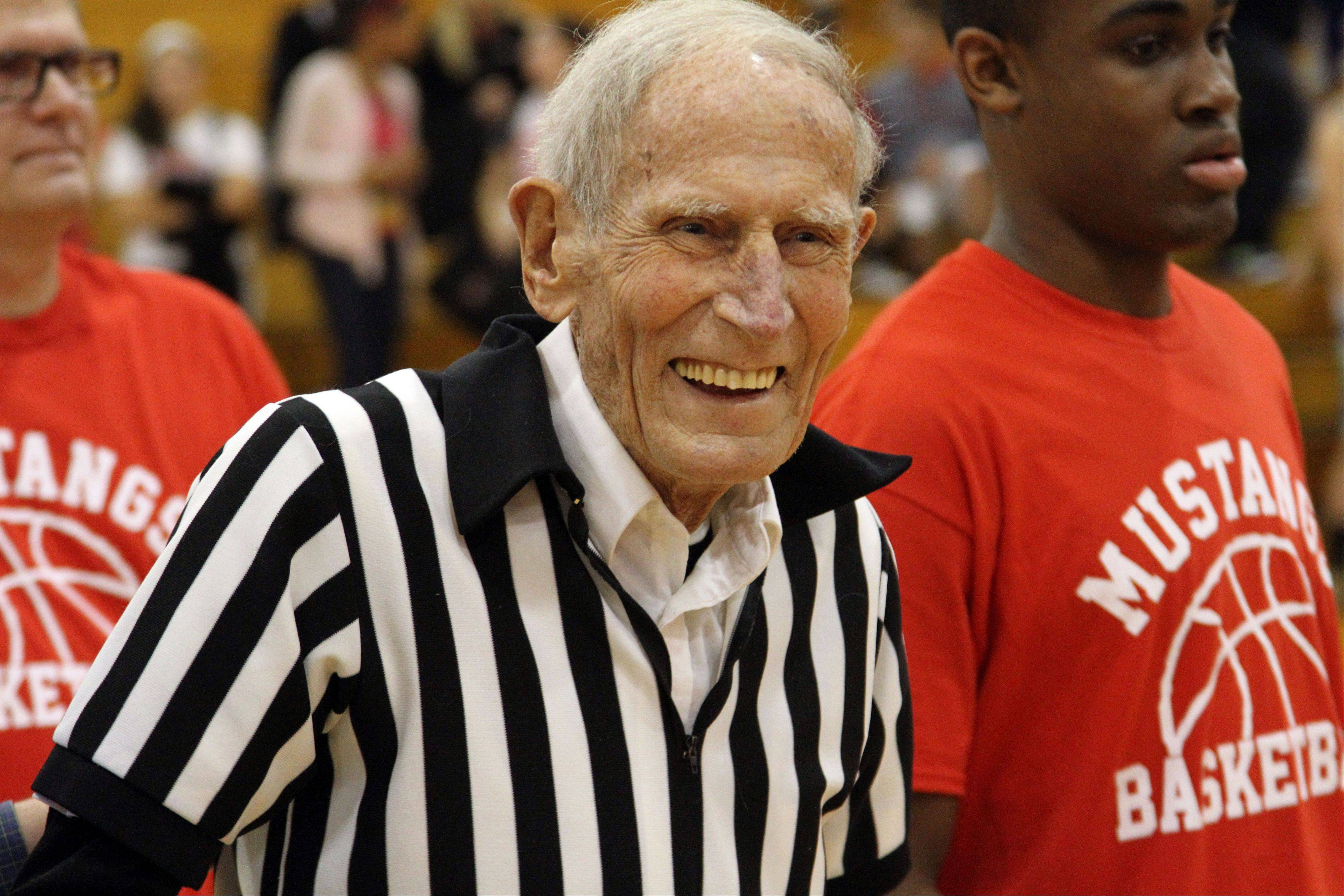Mundelein High School basketball scorekeeper Jim Ackley is all smiles after being honored before Tuesday night's varsity boys basketball game for 50 years of service at Mundelein High School. .