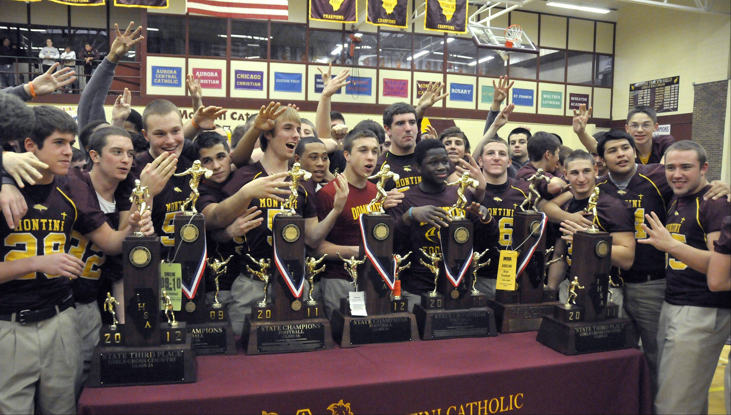 Montini football team members cheer as current and past trophies are displayed Friday afternoon at a pep assembly for winning its fourth consecutive IHSA state football championship last weekend.