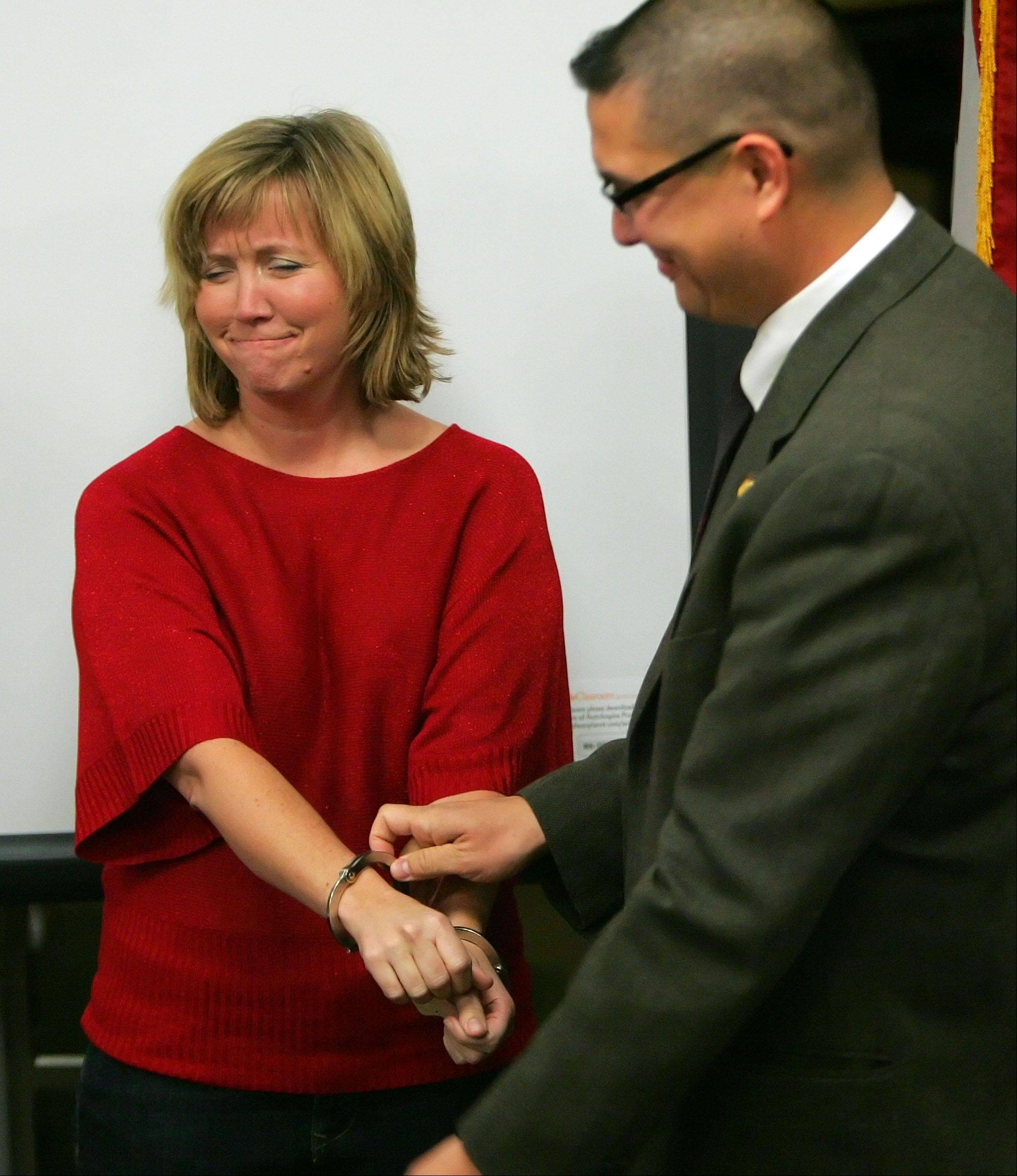 Third grade teacher Kim Zilch, left, plays the roll of an illegal immigrant as courtroom deputy Michael Wing pretends to handcuff her during a visit from U.S. District judge Samuel Der-Yeghiayan at Butterfield School in Libertyville Friday. Der-Yeghiayan is the first Armenian immigrant federal judge in the United States. The students have been involved in a six-week unit on immigration.