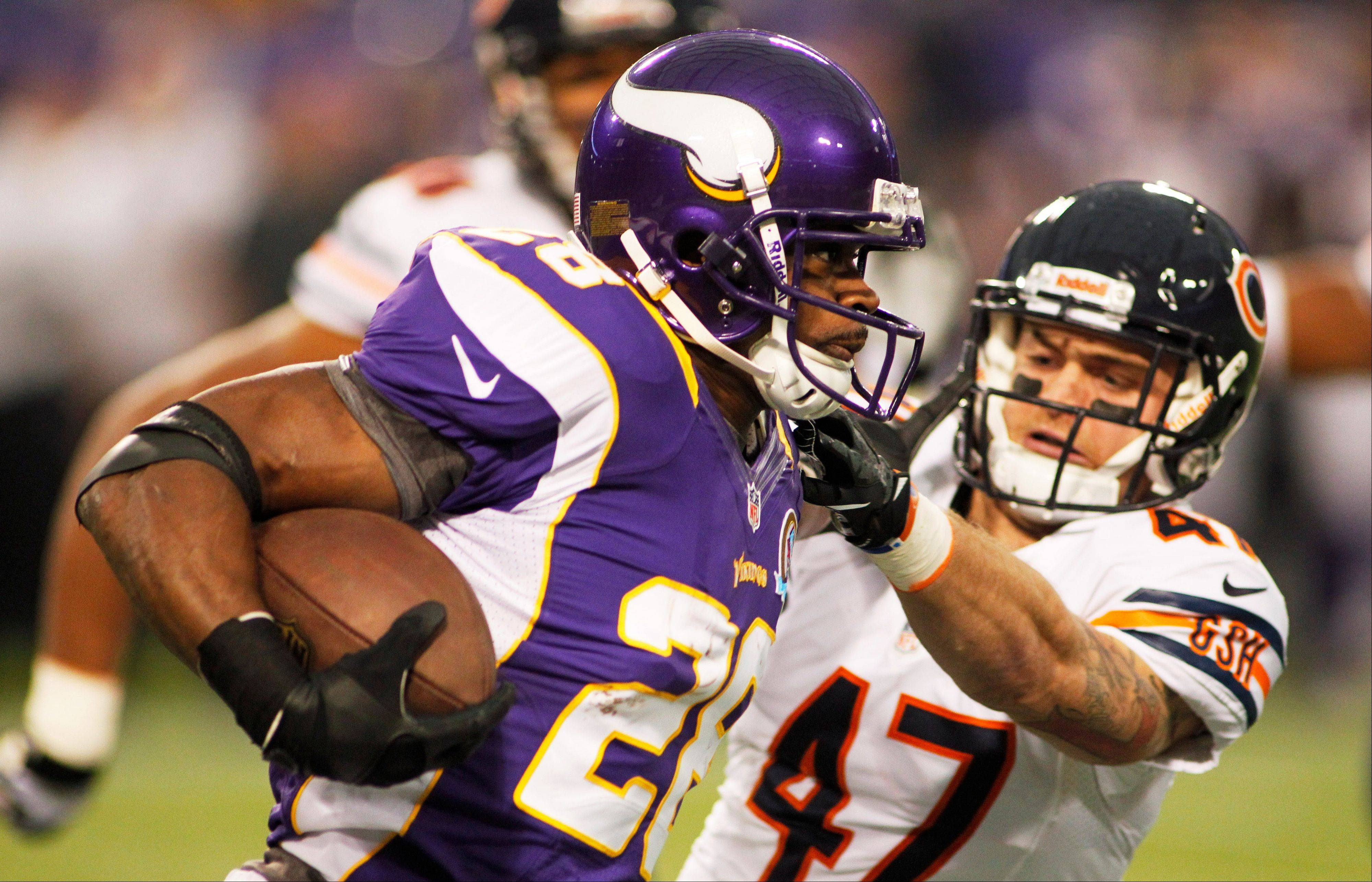 Minnesota Vikings running back Adrian Peterson, left, tries to break a tackle by Chicago Bears safety Chris Conte during the first half of an NFL football game Sunday, Dec. 9, 2012, in Minneapolis.