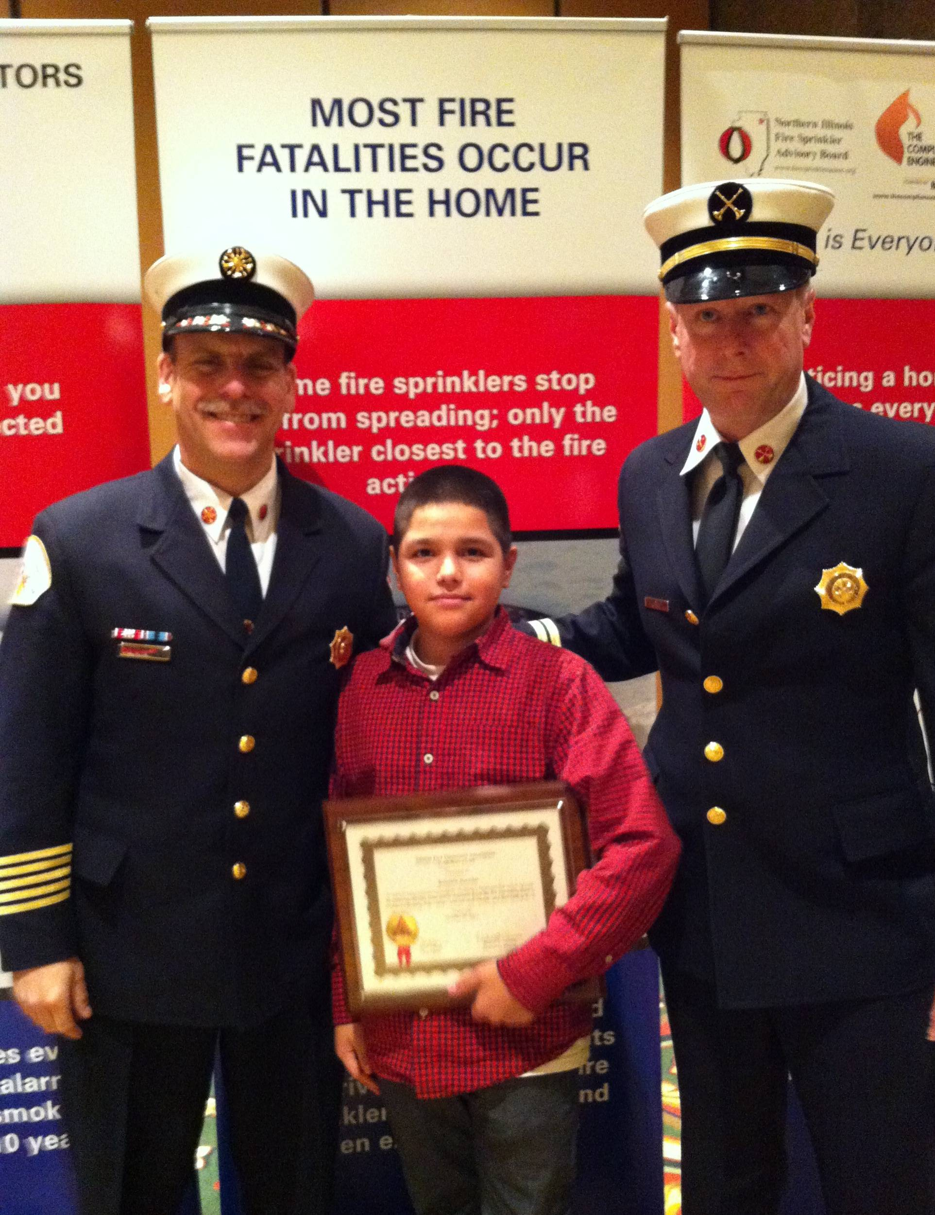 (pictured left to right) Des Plaines Fire Department Chief Alan Wax, Des Plaines resident Benjy Banuelos, displaying the Youth Hero Award, and Division Chief of Fire Prevention Jeff Schuck pose for a photograph in front of a new fire safety banner created by the Inspectors Association at the Illinois Fire Inspectors Association Award Luncheon, Friday, October 26, 2012, at Medinah Banquets, Addison. Banuelos received the award for his actions on Friday, December 23, 2011, when his family's townhouse caught fire in the 1300 block of Fargo Avenue in Des Plaines.