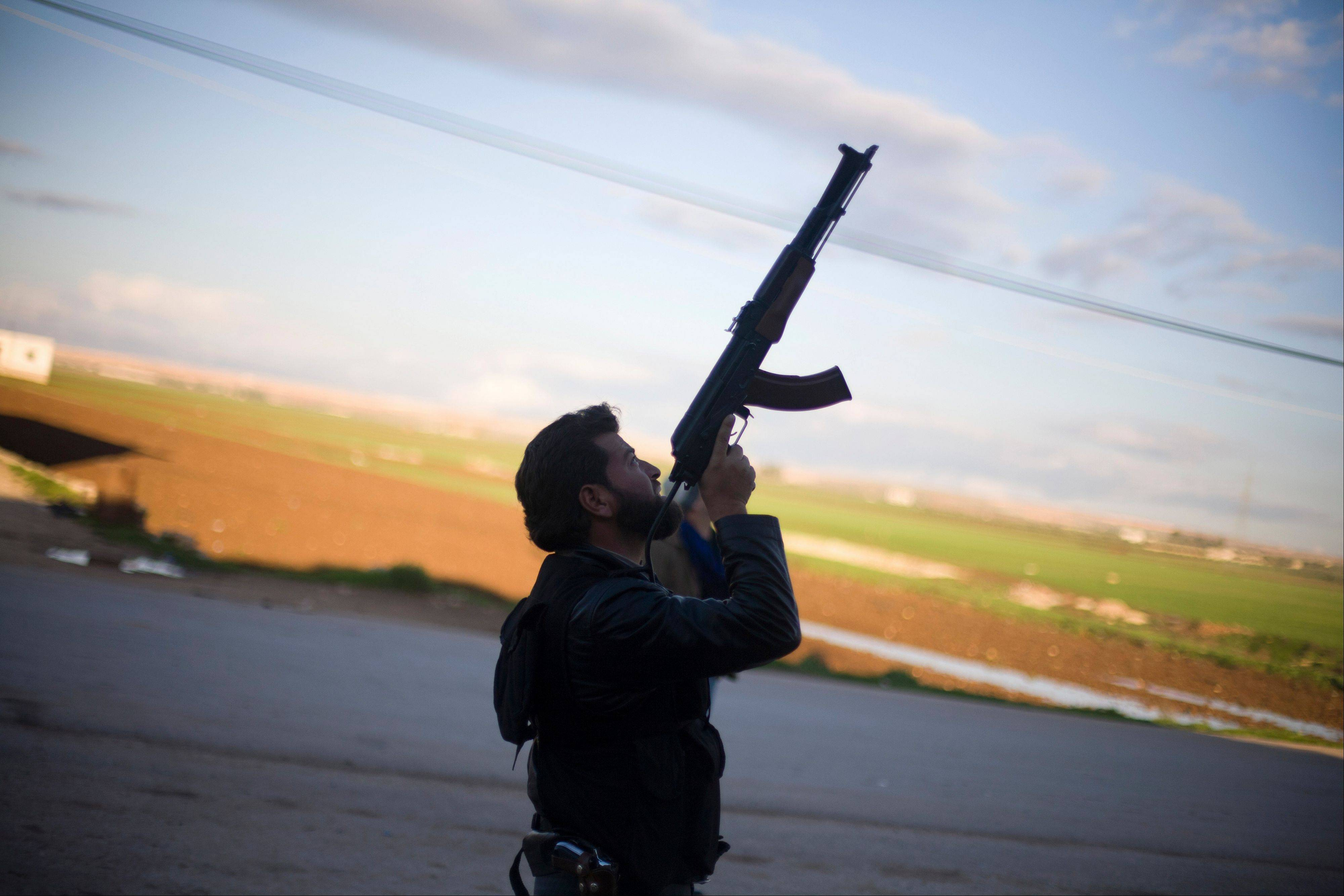 A Free Syrian Army fighter points his weapon Tuesday as he watches a Syrian Army jet, not pictured, in Fafeen village, north of Aleppo province, Syria.
