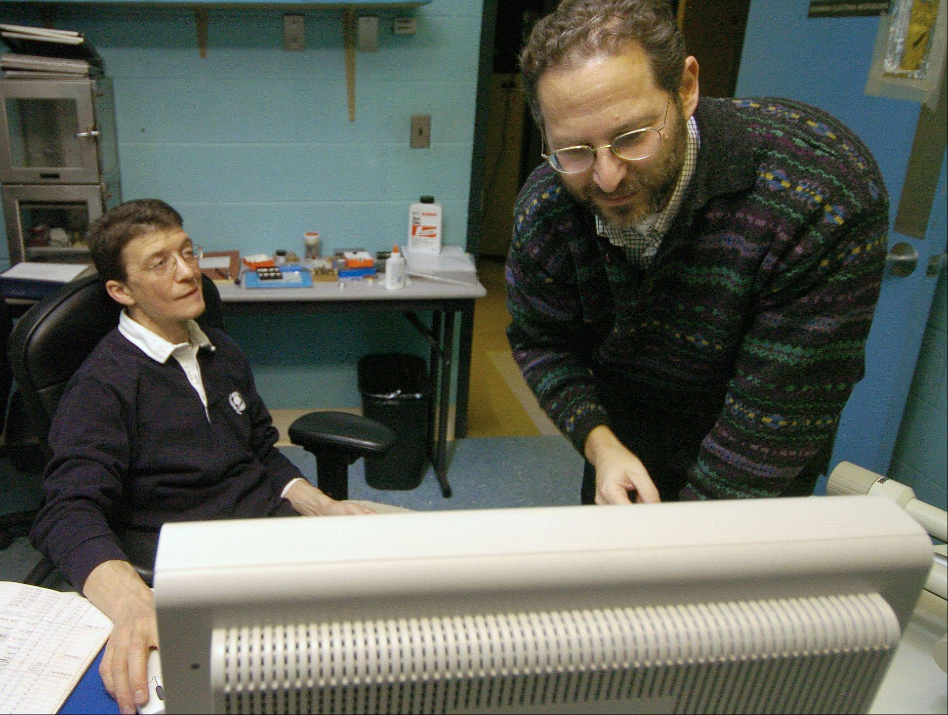 Northern Illinois University geology professor Reed Scherer, right and phD cadidate Matt Olmey examine an image of a single-celled organism gathered in an Antactic core sample. They will spend two months in Antarctica drilling core samples they will use to determine the earth�s climate millions of years ago.