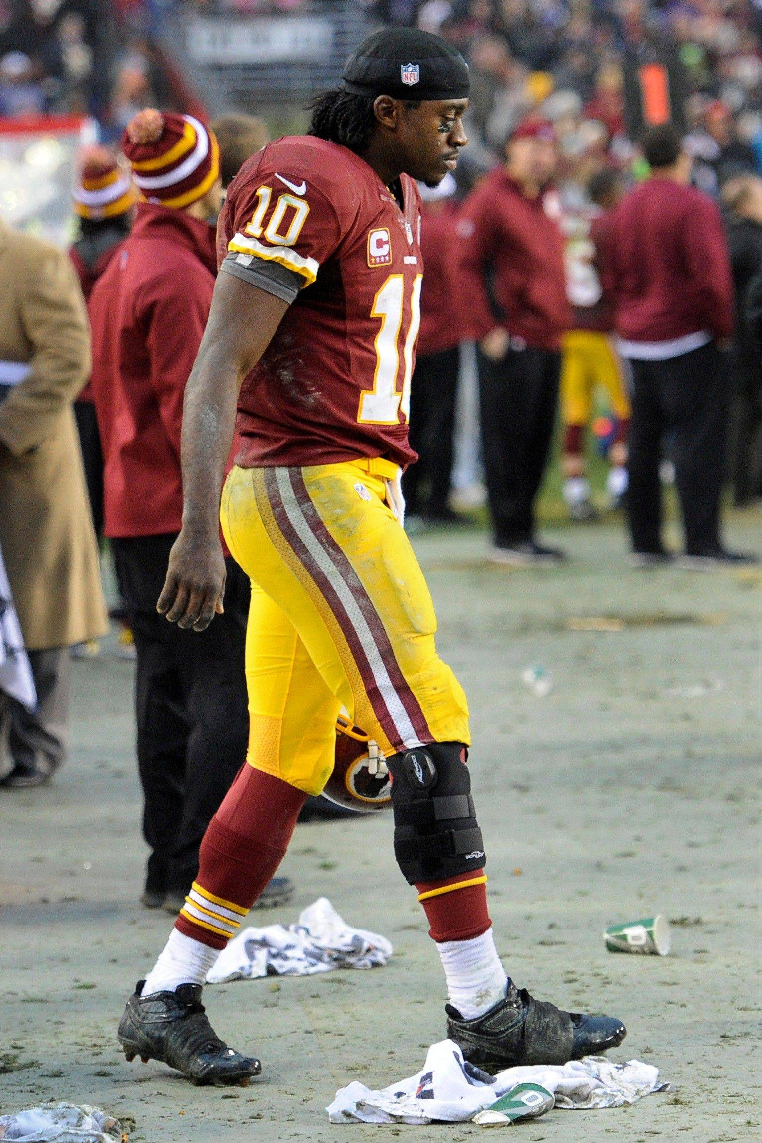 Washington Redskins quarterback Robert Griffin III walks through the bench area with a brace on his knee during overtime of Sunday�s game against the Ravens at Baltimore.