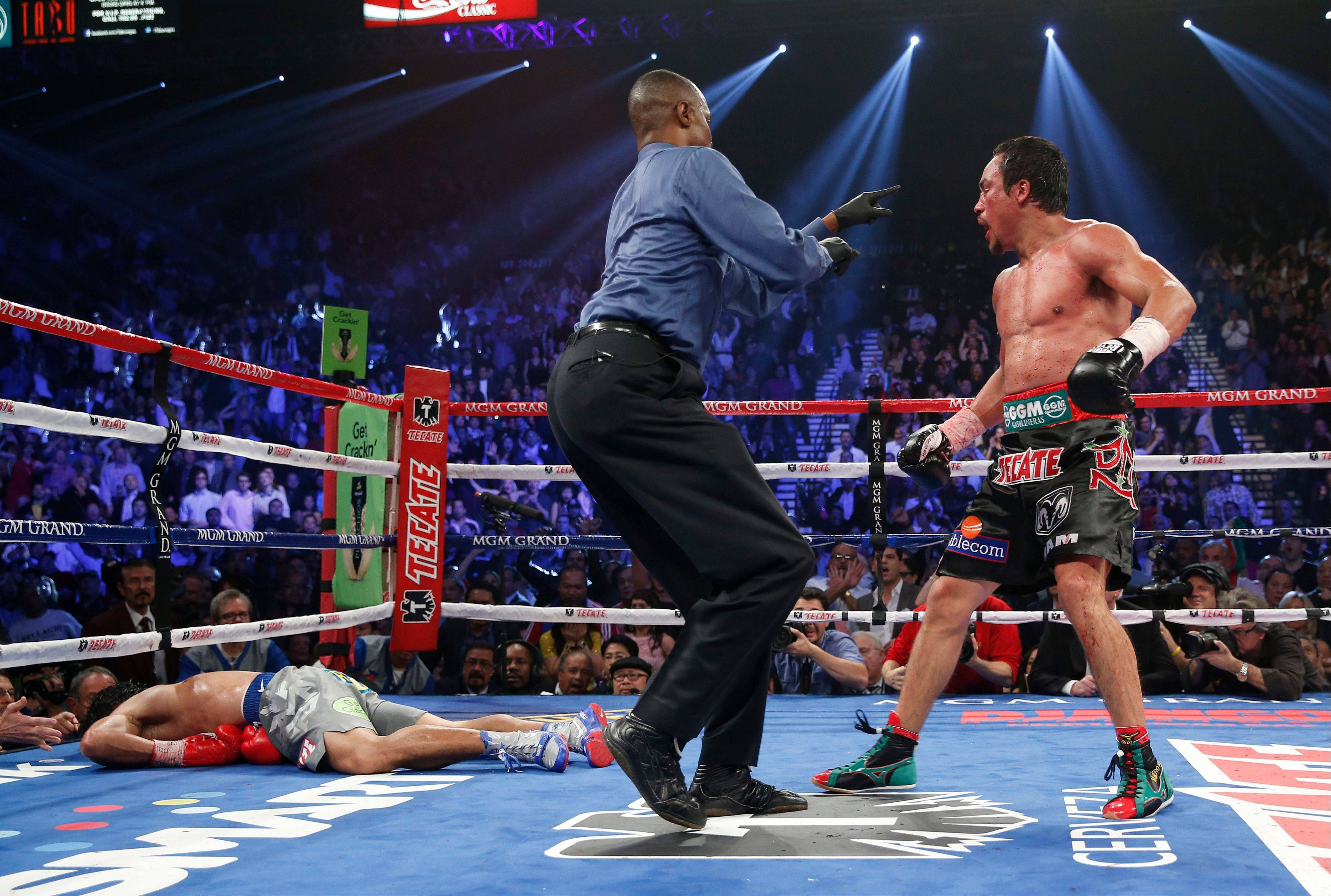 Referee Kenny Bayless sends Juan Manuel Marquez to his corner after Marquez knocked out Manny Pacquiao in the sixth round of their WBO world welterweight fight Saturdayin Las Vegas.