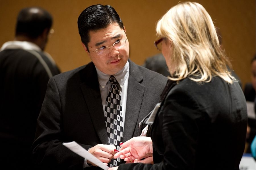 A job seeker, left, speaks with a recruiter during a HIREvent job fair Tuesday in San Jose, California.