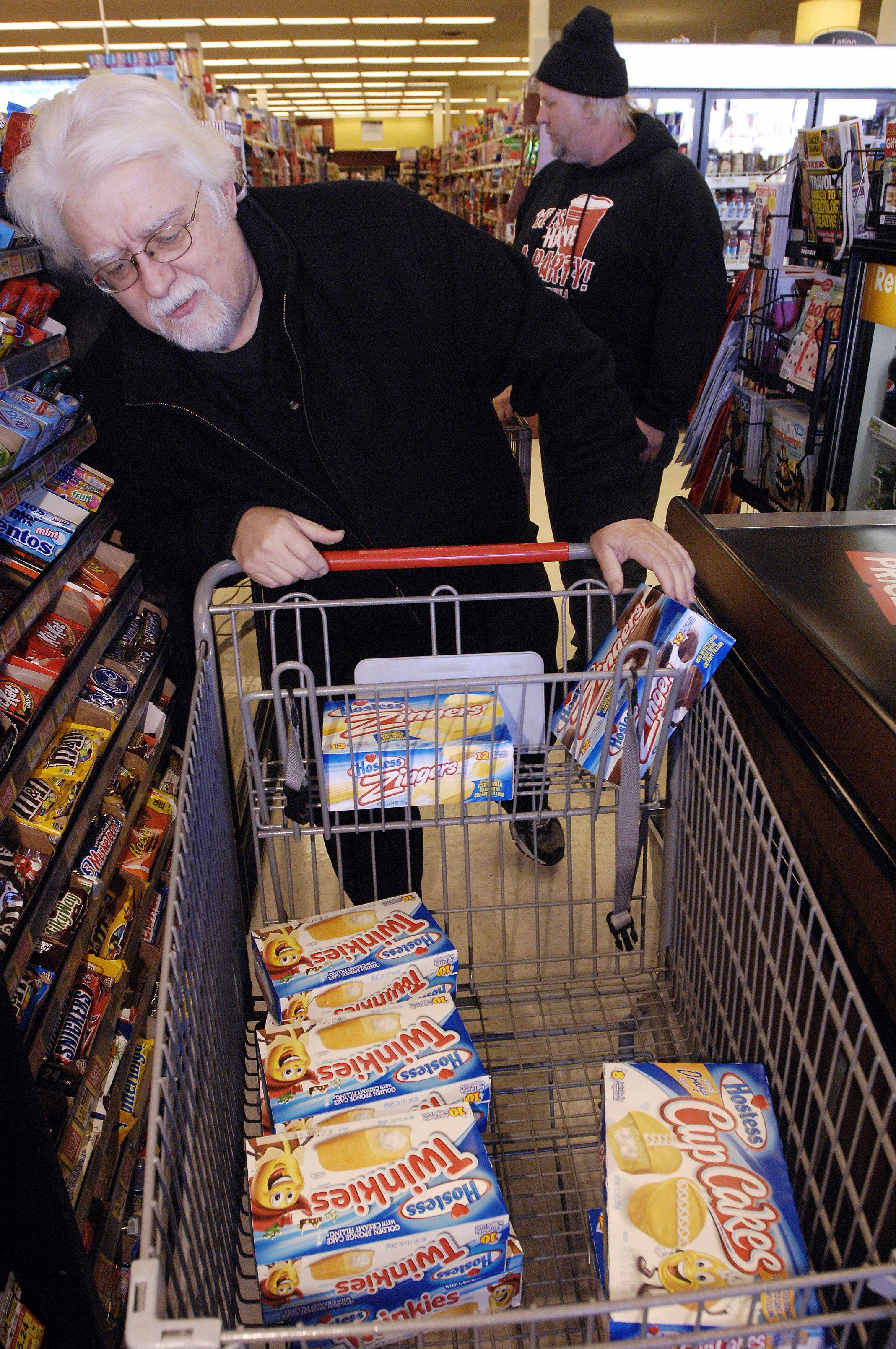 Customer Bob Gunnison of Carol Stream counts the boxes for the cashier Tuesday morning after snatching up the last of the Twinkies at the Jewel-Osco in downtown Wheaton.