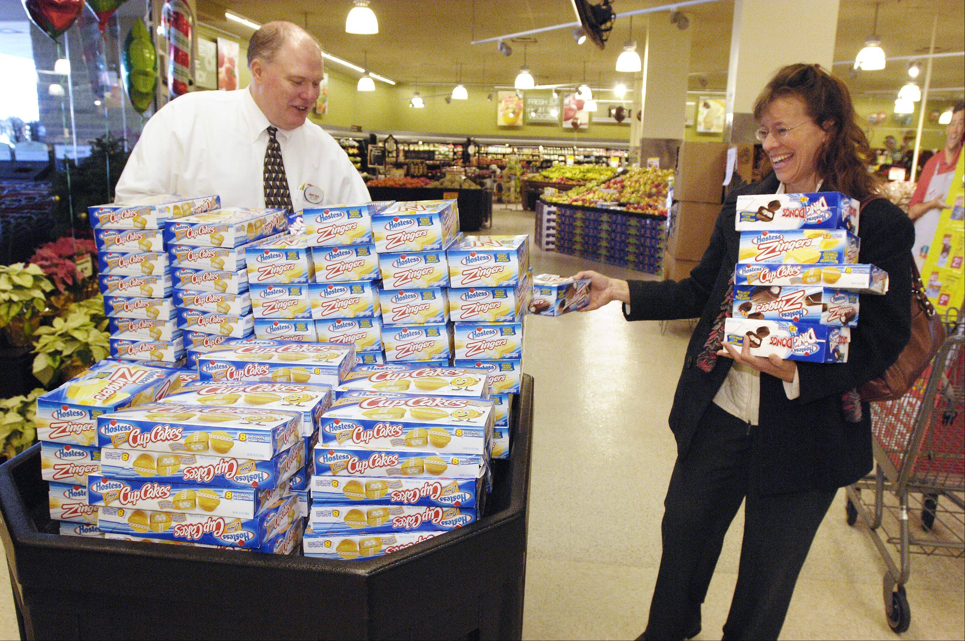 Wheaton Jewel Store Director Jim Primm unloads Hostess products as customer Jennifer Humecke picks a variety of products Tuesday.