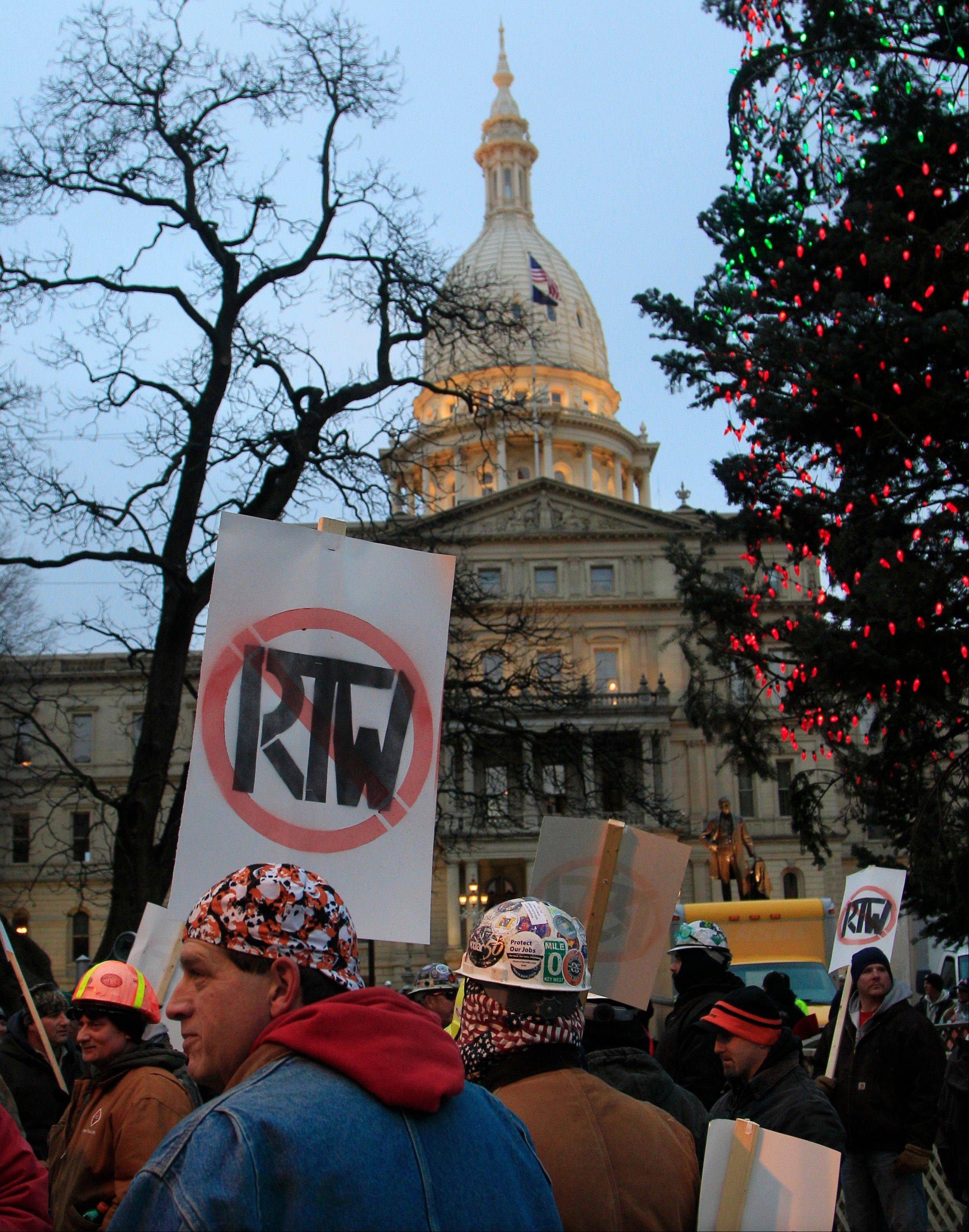 People begin gathering outside on the State Capitol grounds in Lansing, Mich., Tuesday, Dec. 11, 2012 to protest right-to-work legislation that was passed by the state legislature last week. Michigan will become the 24th right-to-work state, banning requirements that nonunion employees pay unions for negotiating contracts and other services.