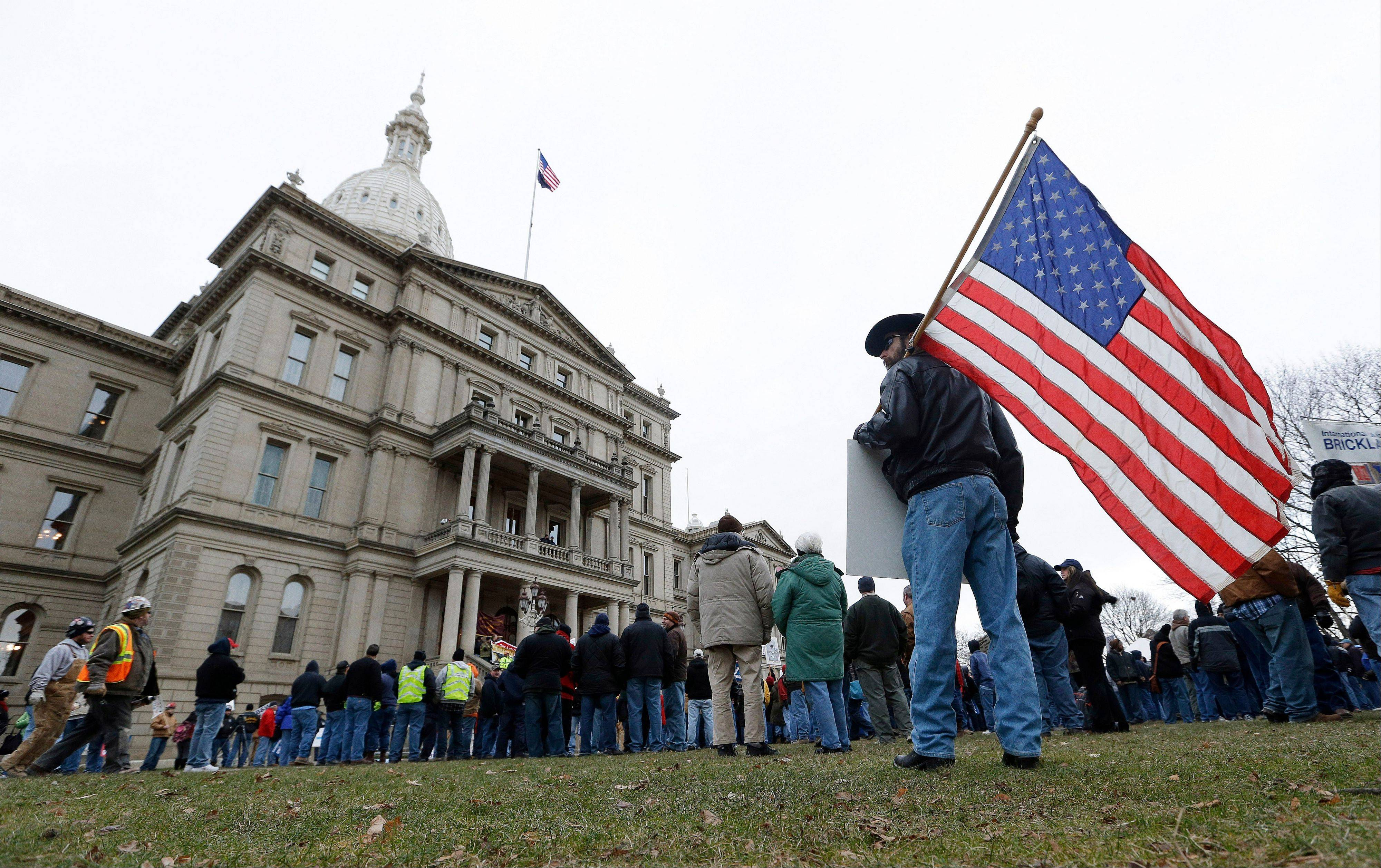 A protester holds an American flag at a rally on the State Capitol grounds in Lansing, Mich., Tuesday, Dec. 11, 2012.