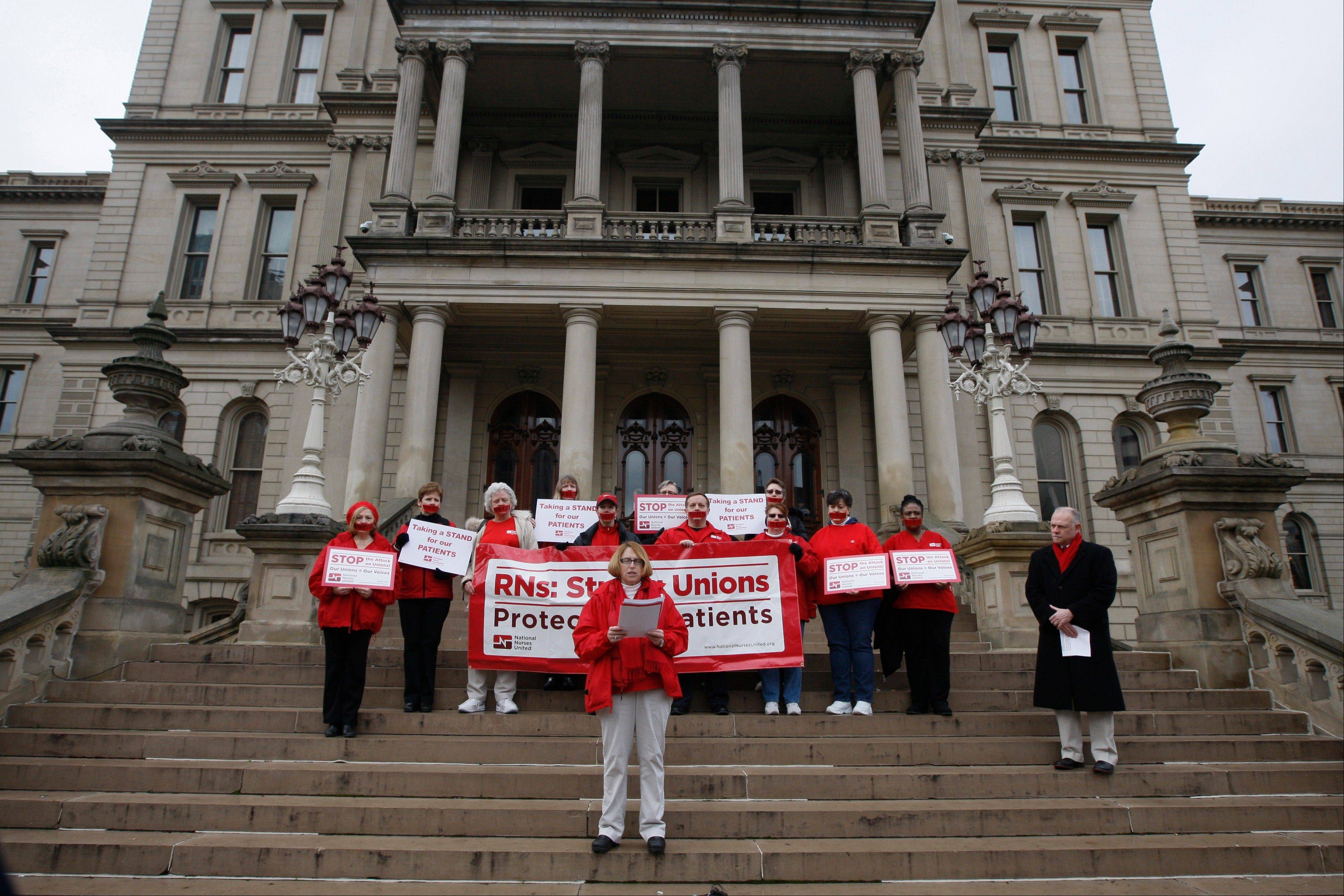 About a dozen members of the Michigan Nurses Association stand on the state Capitol steps in Lansing, Mich., Monday protesting right-to-work legislation. Organizers say the gathering was meant to symbolize the silencing of unions that nurses say will happen should the legislation become law.
