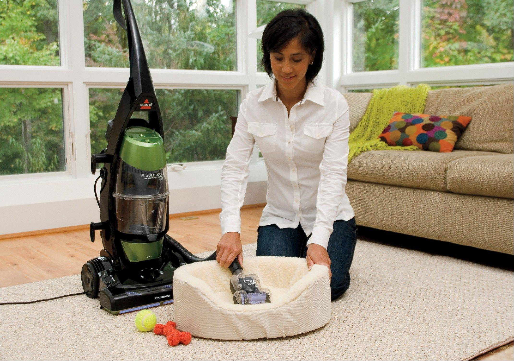 A woman using a BISSELL Total Floors Pet Vacuum that features a crevice tool port to suction pet hair away from walls where it accumulates without reaching or bending.