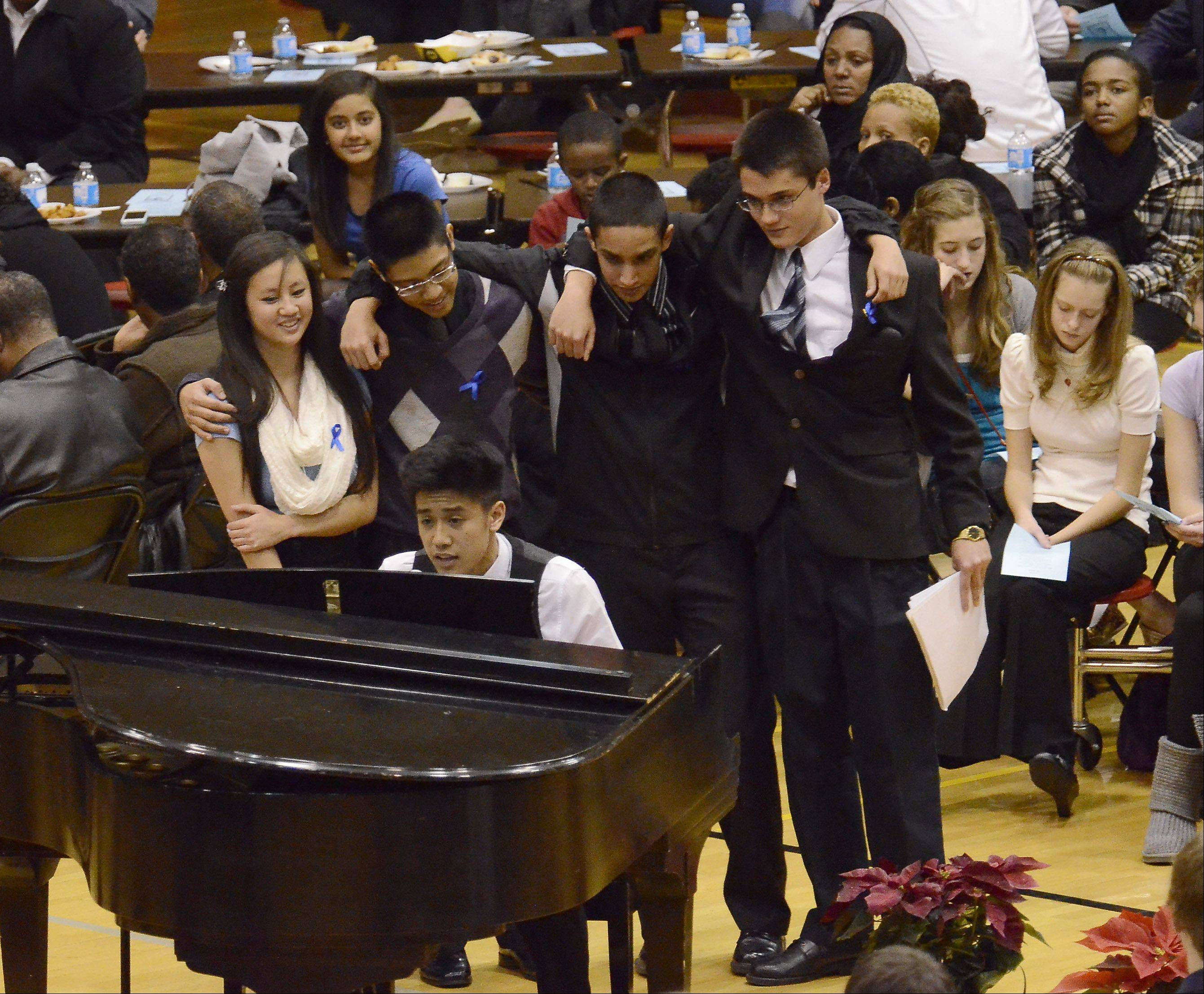 "Jan Dimaano plays ""Let It Be"" on the piano as other friends of Schaumburg student Mikias Tibebu join in at a memorial service Thursday in the school gym."