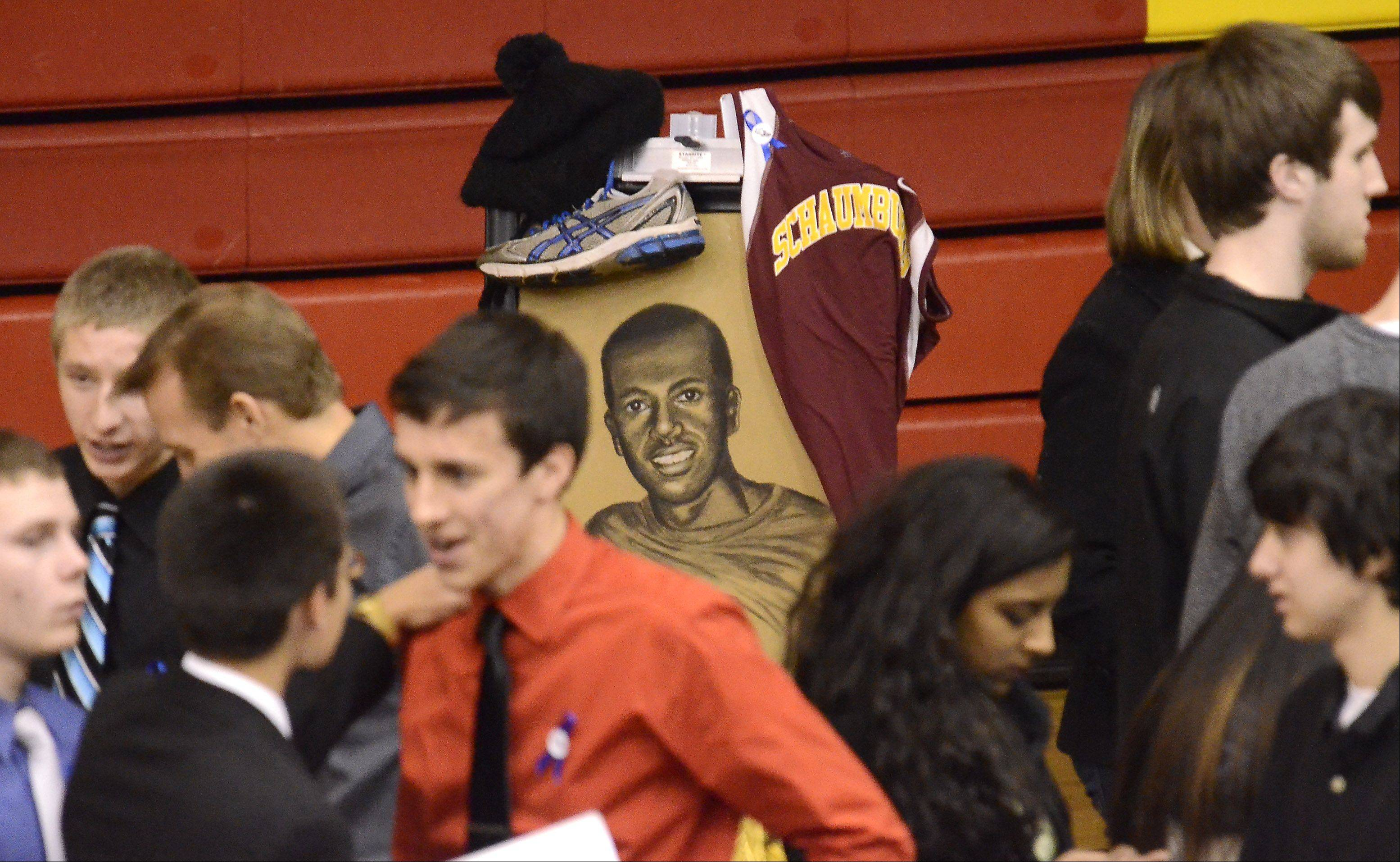 A portrait of Schaumburg student Mikias Tibebu looks back at his friends and classmates at a memorial service for him Thursday in the school gym. The portrait was done by Olivia Zubko.