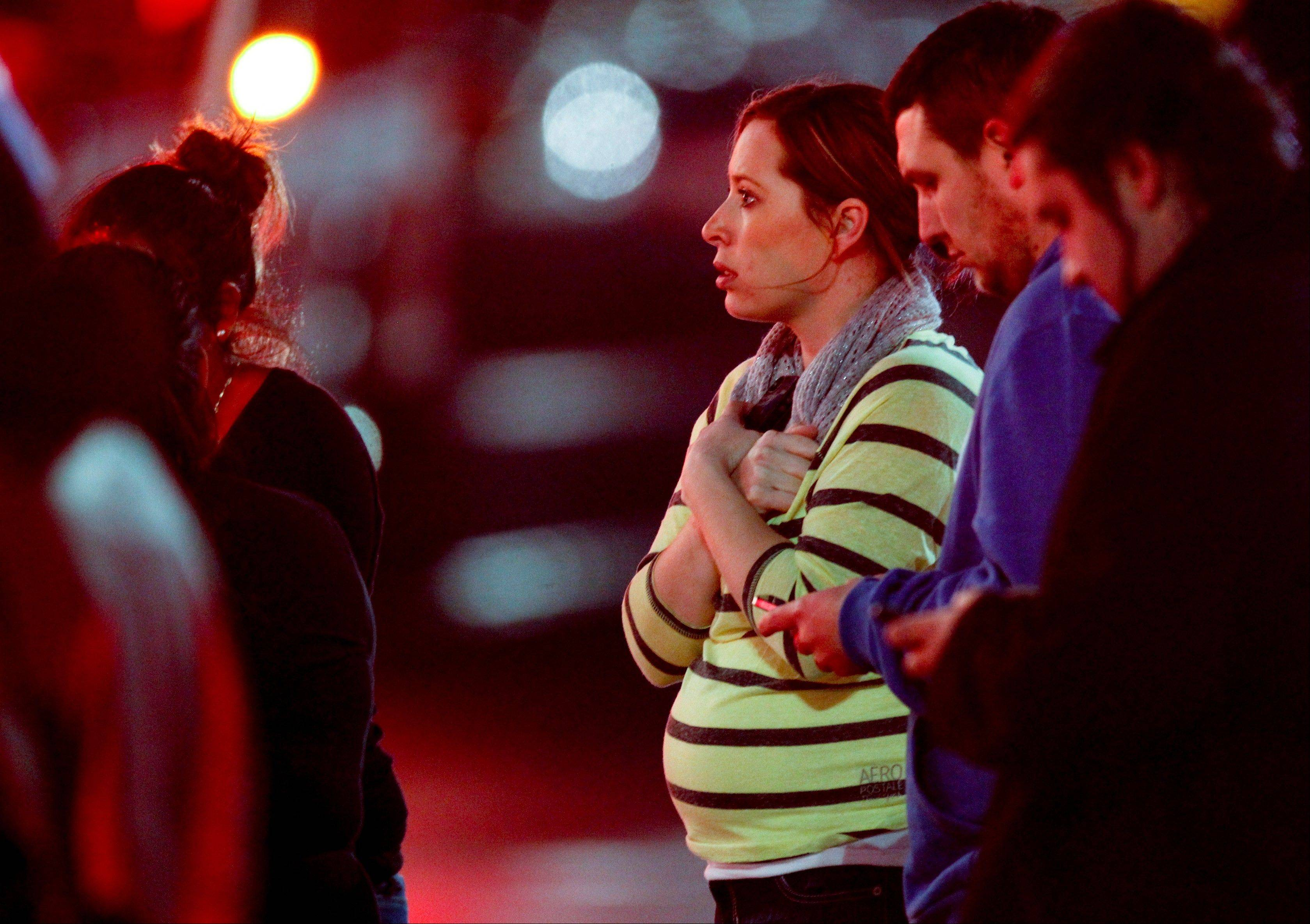 Onlookers observe the scene outside Clackamas Town Center in Portland, Ore., where a shooting occurred Tuesday, Dec. 11, 2012.