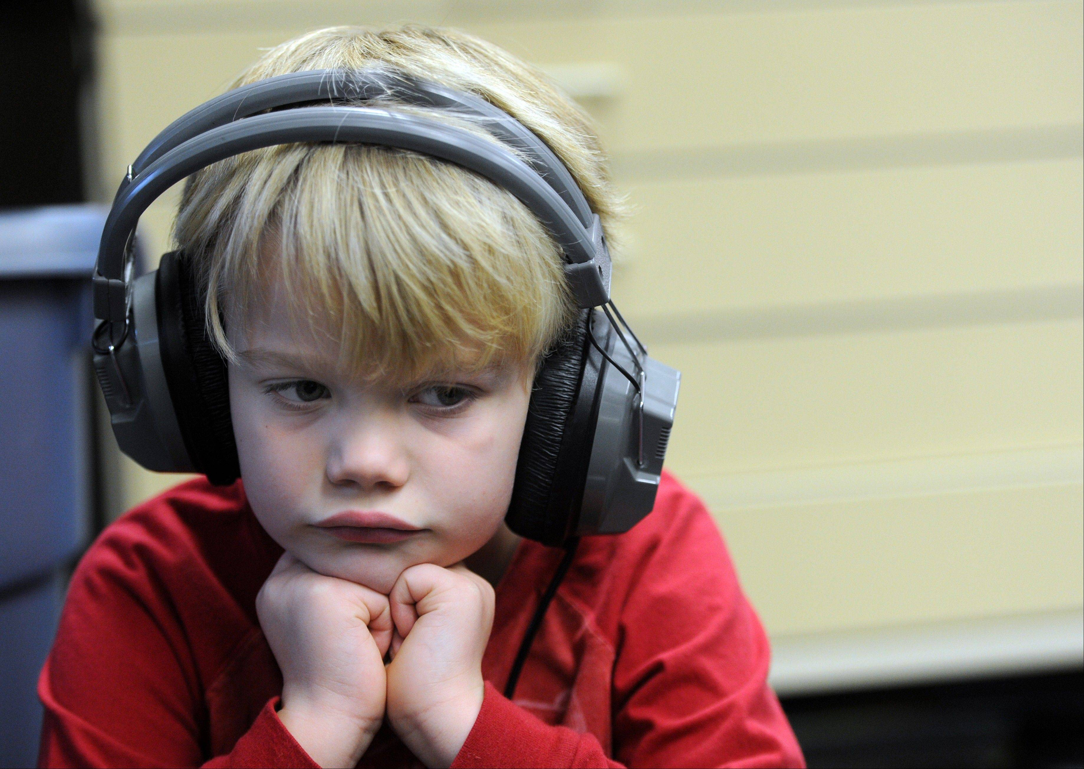 Kindergartener Brayden Baize listens to a narrated book Monday during one of their daily reading stations at Stringtown Elementary School in Evansville, Ind.