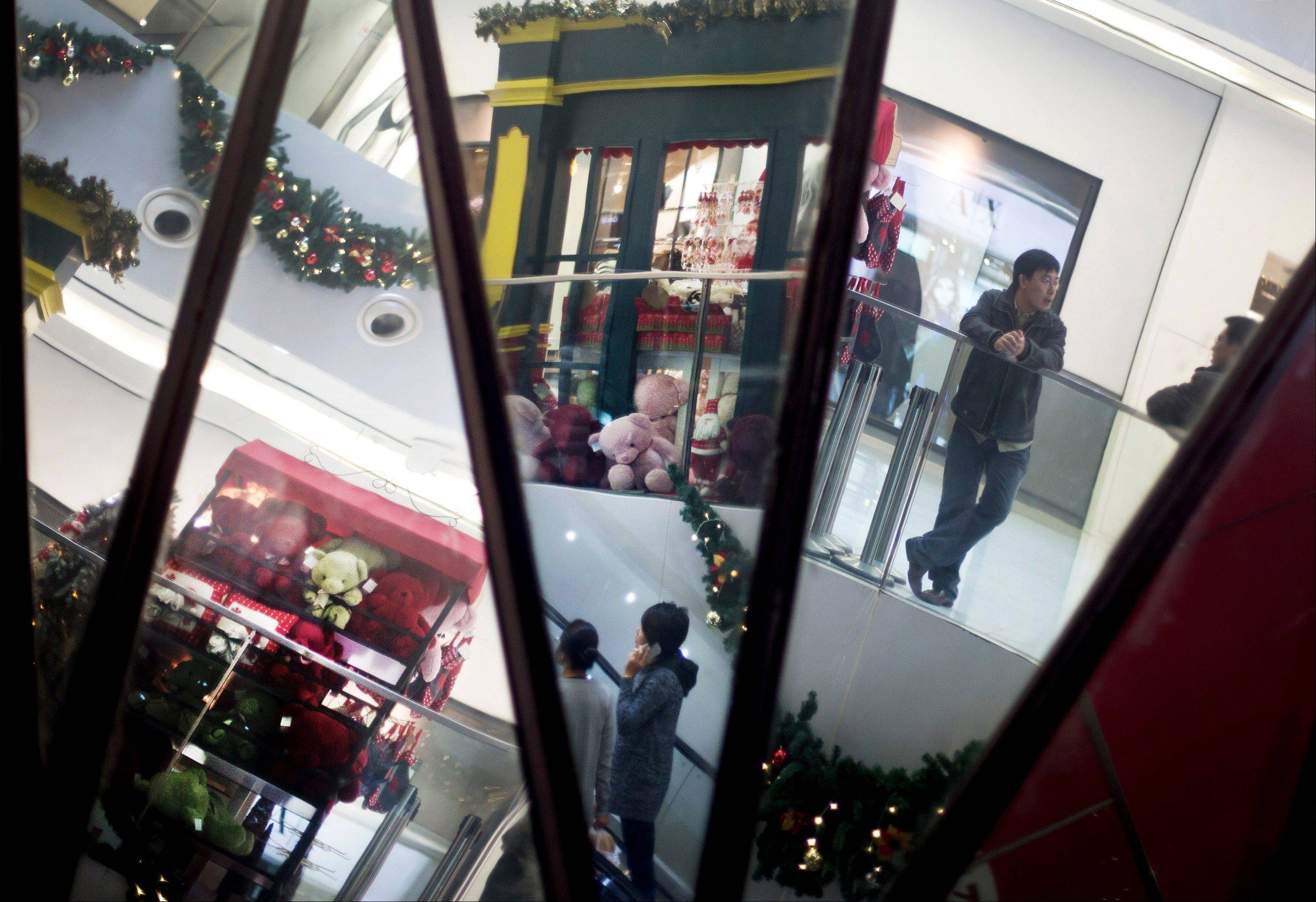 Chinese shoppers and Christmas decorations are reflected in mirrors inside a shopping mall Monday in Beijing. China's trade weakened sharply in November, adding to challenges for the world's second-largest economy as a gradual recovery takes shape. Export growth plunged to 2.9 percent over a year earlier from the previous month's 11.6 percent.