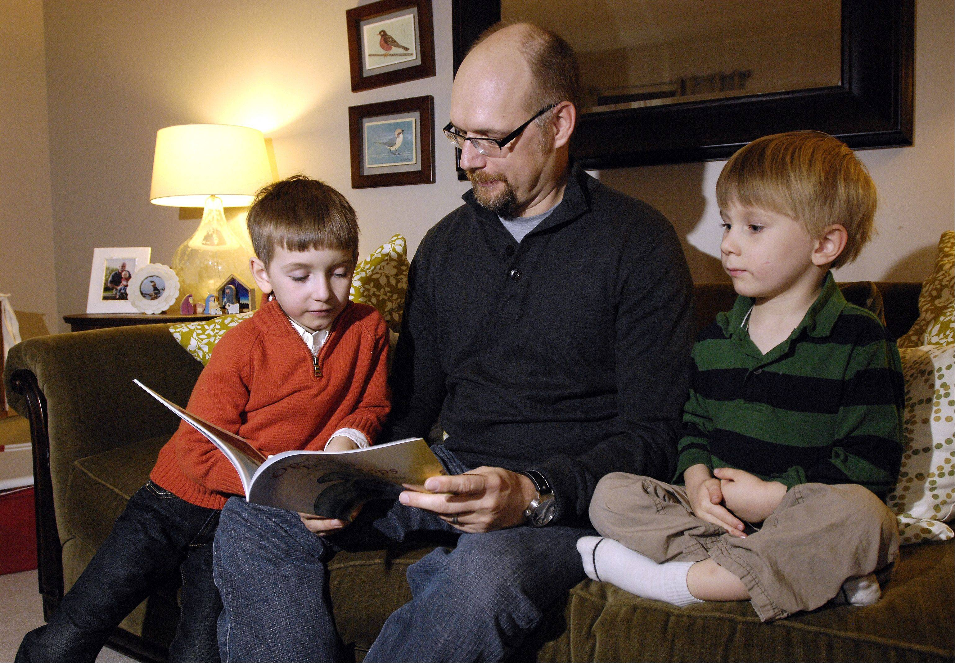 "Naperville North High School English teacher Mitch Martin reads to his sons, Soren and Alec, from his new children's book, ""Op-Op the Triceratops: A Cretaceous Christmas Tale."" Martin says he was inspired to write the 24-page, brightly illustrated book to help teach his kids, and others, to value their family and not their wish list."