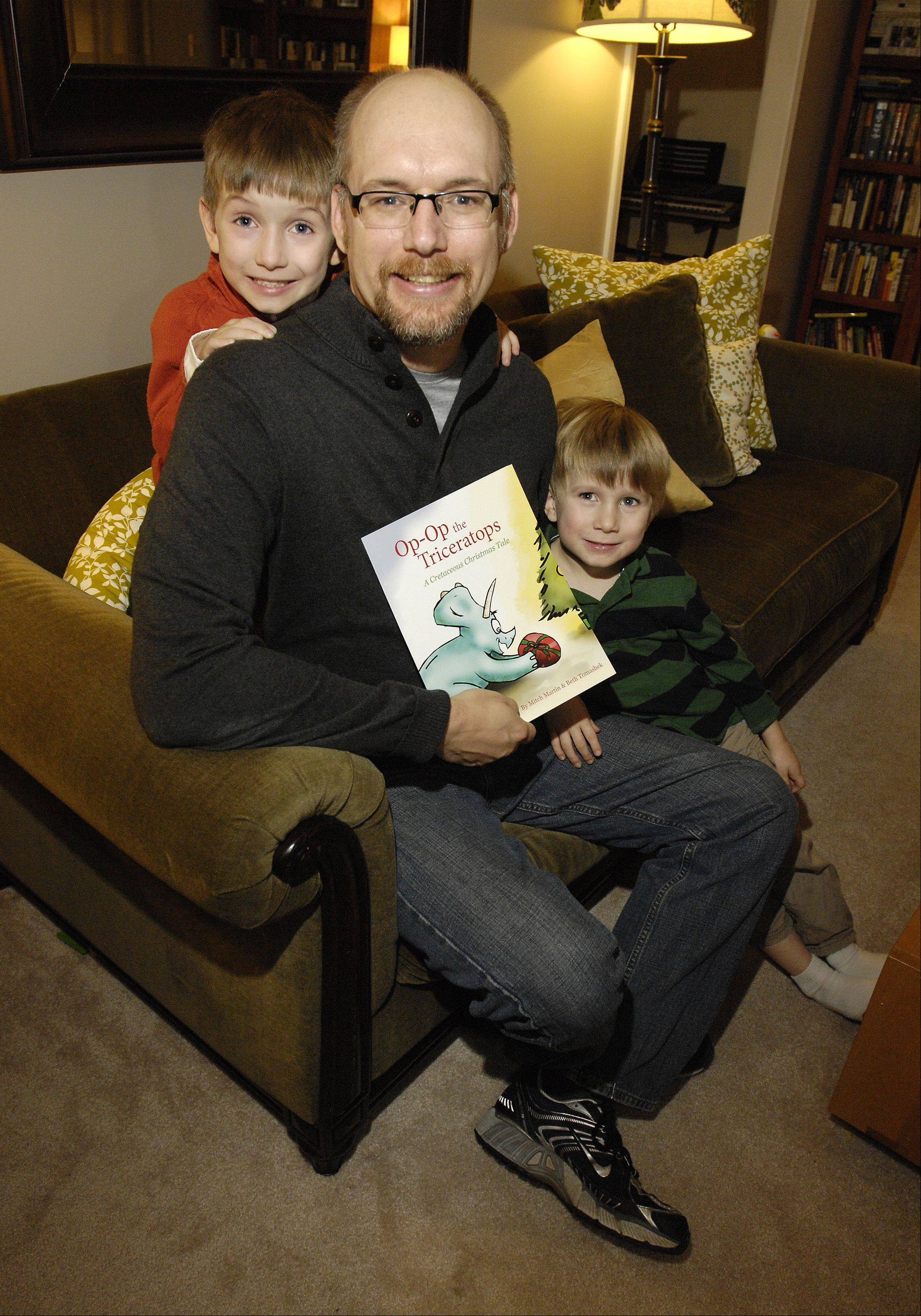 "Mitch Martin at his Lisle home with sons Soren and Alec, who served as an inspiration for his first book, ""Op-Op the Triceratops: A Cretaceous Christmas Tale."""