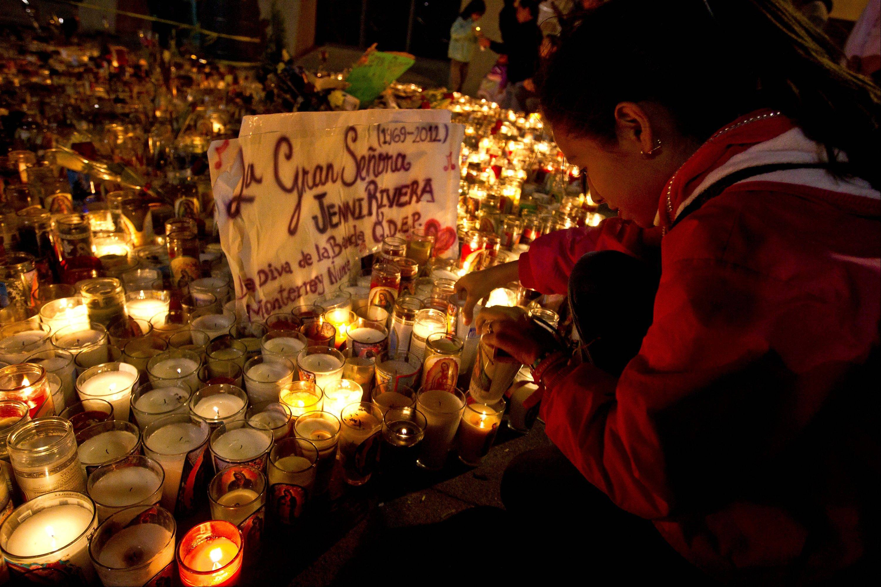 A fan of Jenny Rivera lights a candle at the Basilica of Guadalupe in the city of Monterrey, Mexico, Monday Dec. 10, 2012. U.S. authorities confirmed Monday that Rivera, a U.S.-born singer whose soulful voice and openness about her personal troubles made her a Mexican-American superstar, was killed in a plane crash early Sunday in northern Mexico.