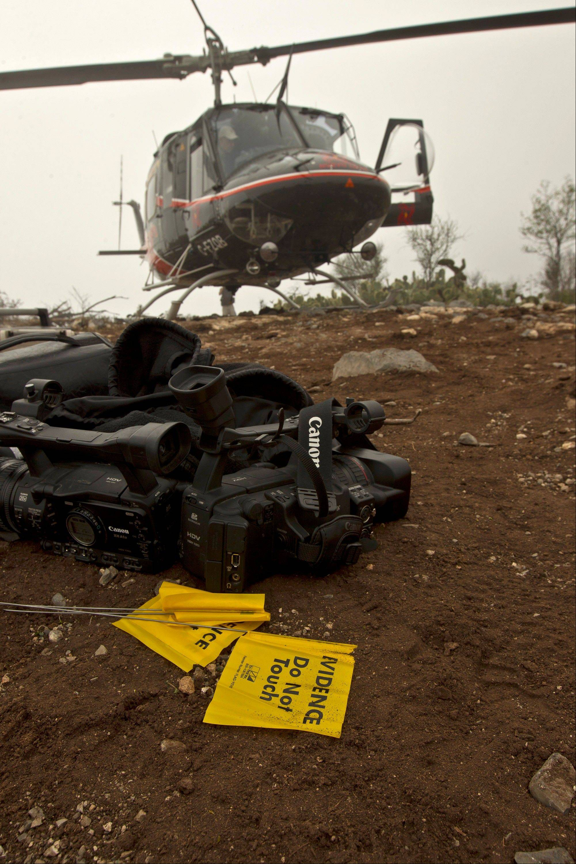 Video cameras and flags used by the forensic experts are unloaded from a helicopter on top of the hill next to the canyon where an airplane crash occurred a day earlier claiming the life of U.S.-born singer Jenni Rivera near the town of Iturbude, Mexico, Monday Dec. 10, 2012. The crash in northern Mexico also killed six friends and co-workers.