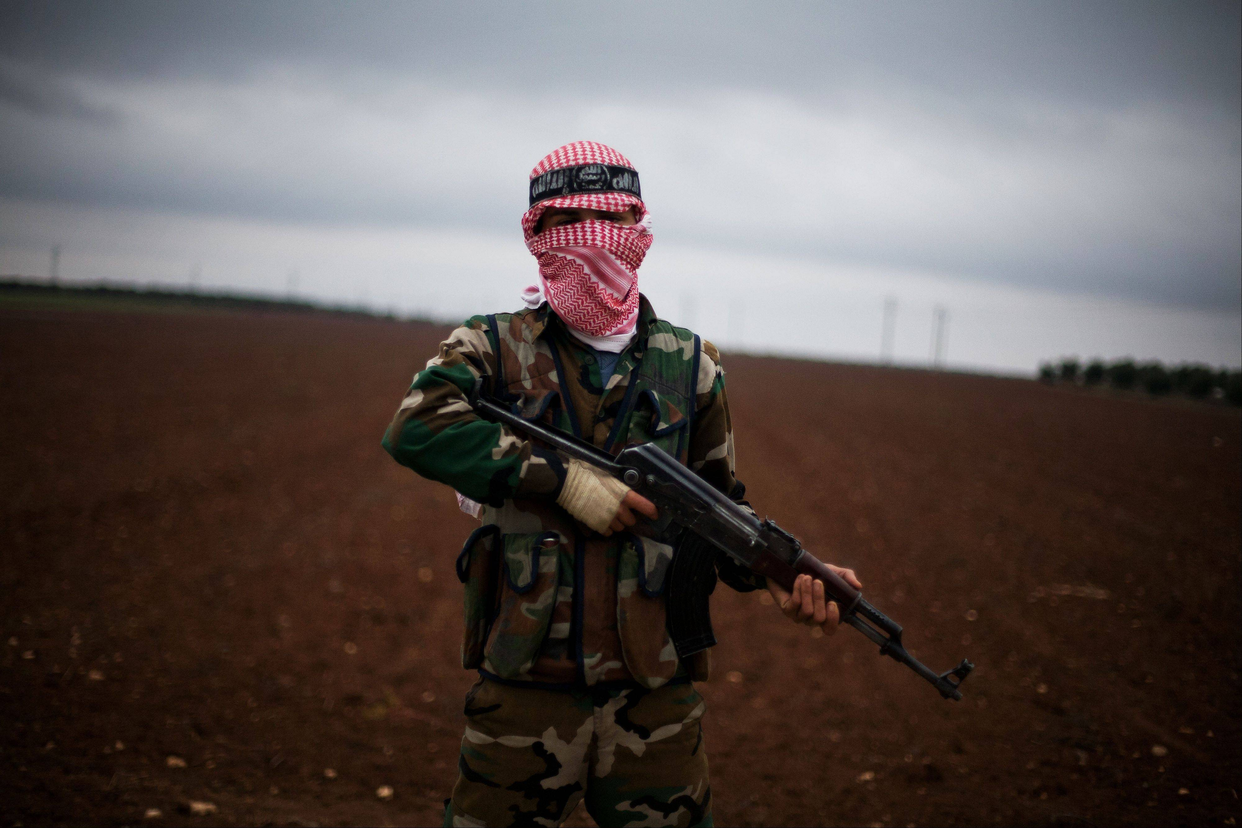 A Free Syrian Army fighter takes position close to a military base, near Azaz, Syria, Monday, Dec. 10, 2012. The gains by rebel forces came as the European Union denounced the Syrian conflict, whi