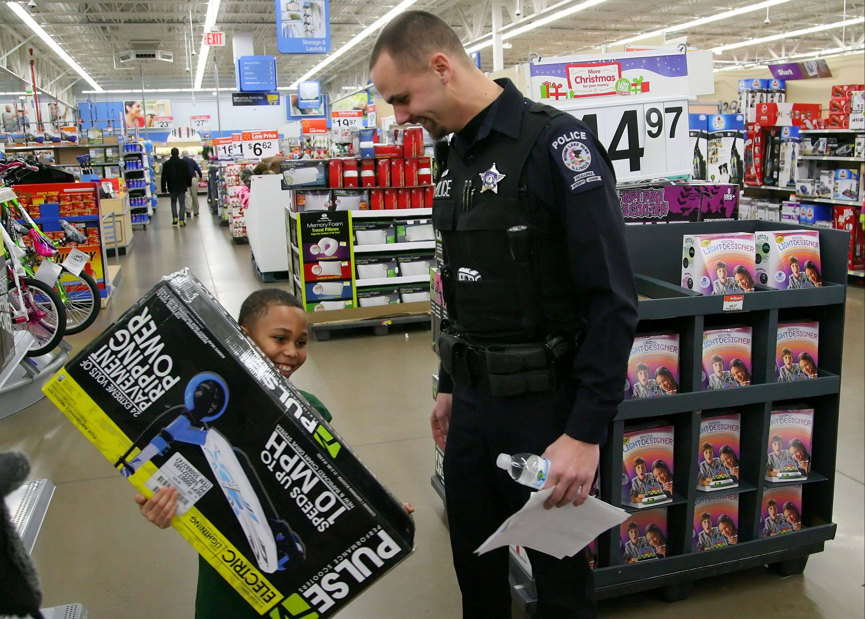 Round Lake Park police officer Steve Sliozis helps 9-year-old Demar Hill of Hainesville select Christmas presents during Monday's Shop with a Cop at Walmart in Round Lake Beach. It was the 17th consecutive year Round Lake Park police put together Lake County's original Shop with a Cop program.