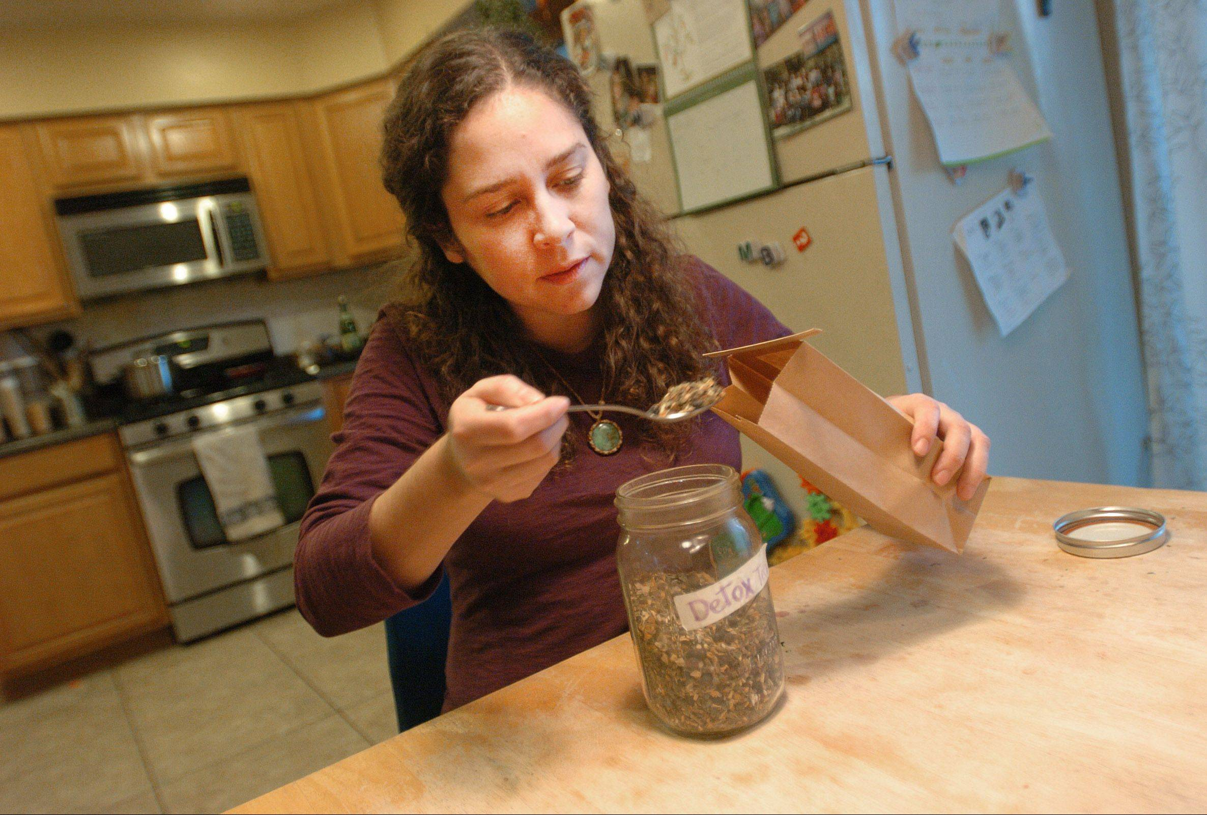 Cote Garceau-Saez of Aurora, owner of Our Healing Roots, packs a bag with a tea, which she says will be used to help the immune system fend off colds. For her home remedies, she collects most of what she needs from local fields and privately owned forested areas, but also gets some supplies from organic vendors.